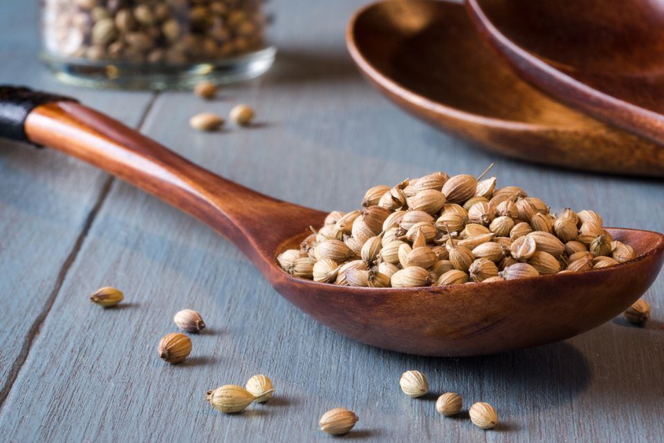 Close-Up Of Coriander Seeds In Wooden Spoon On Table
