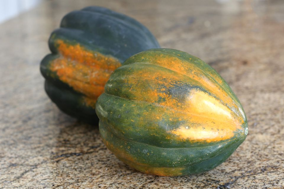 Two whole acorn squash on a marble slab