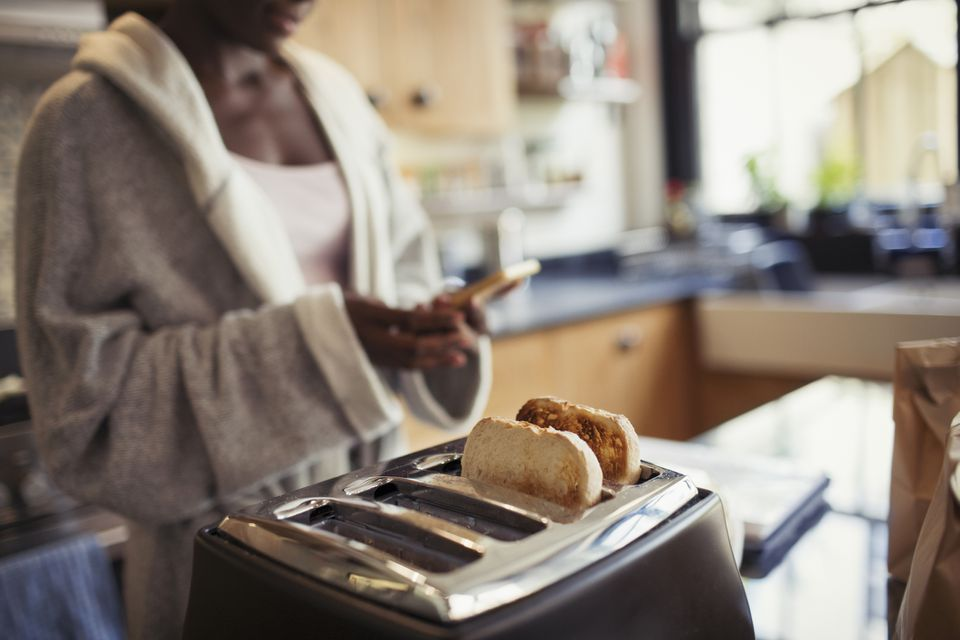 Woman texting in front of toaster