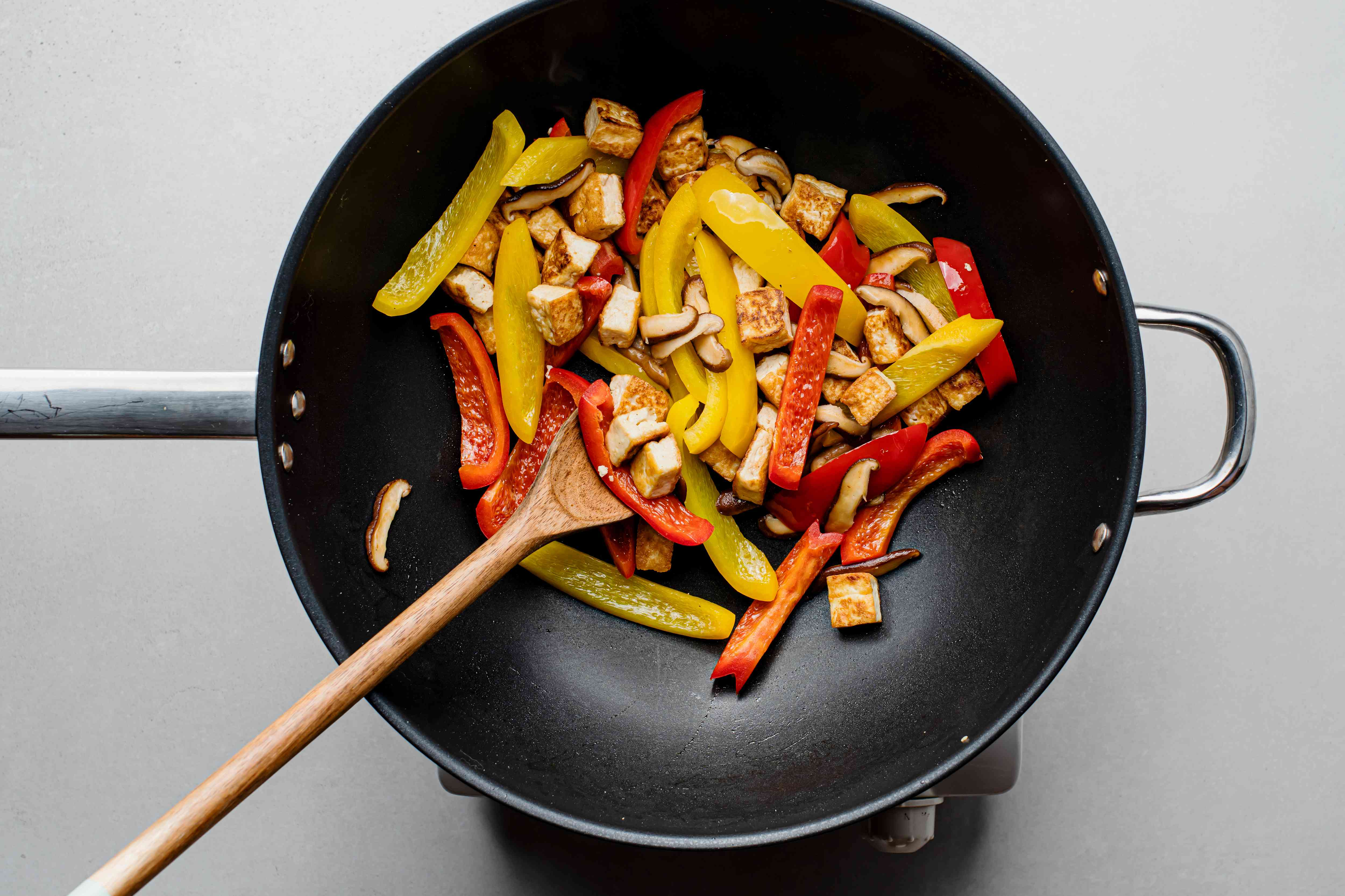 tofu with peppers and mushrooms in a wok