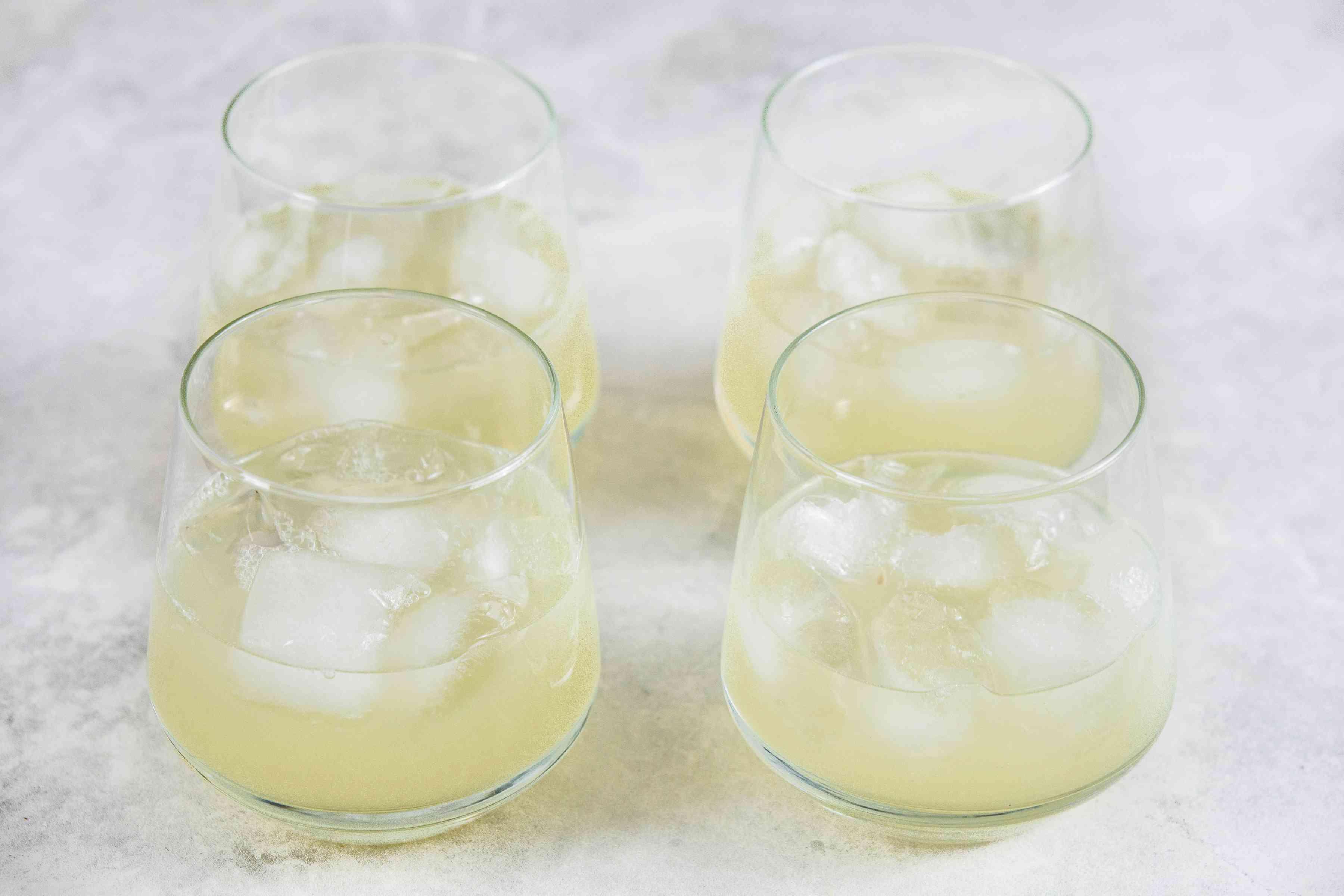 Divide lime juice between glasses