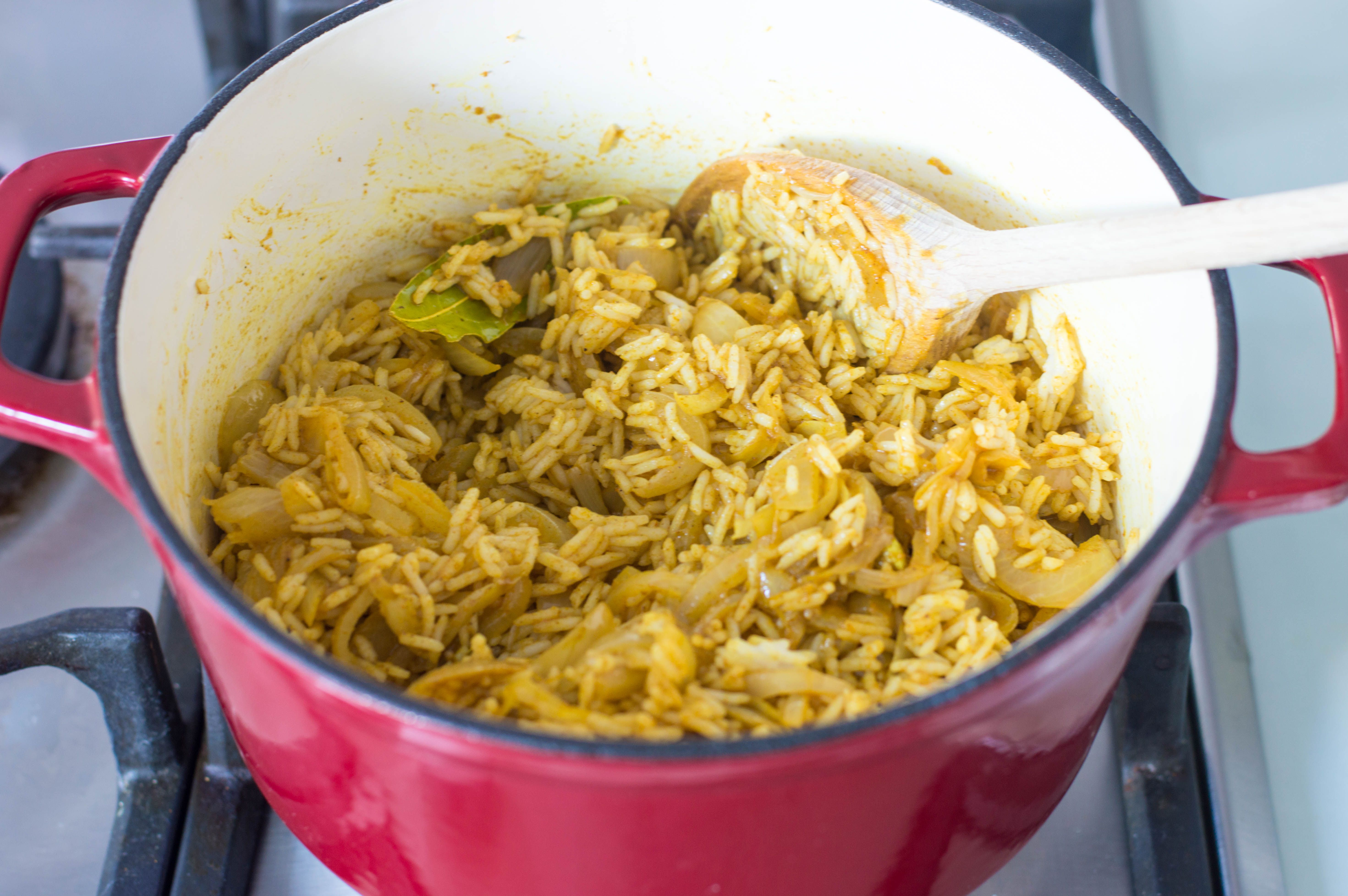 Rice, curry, and onions in a pan for kedgeree