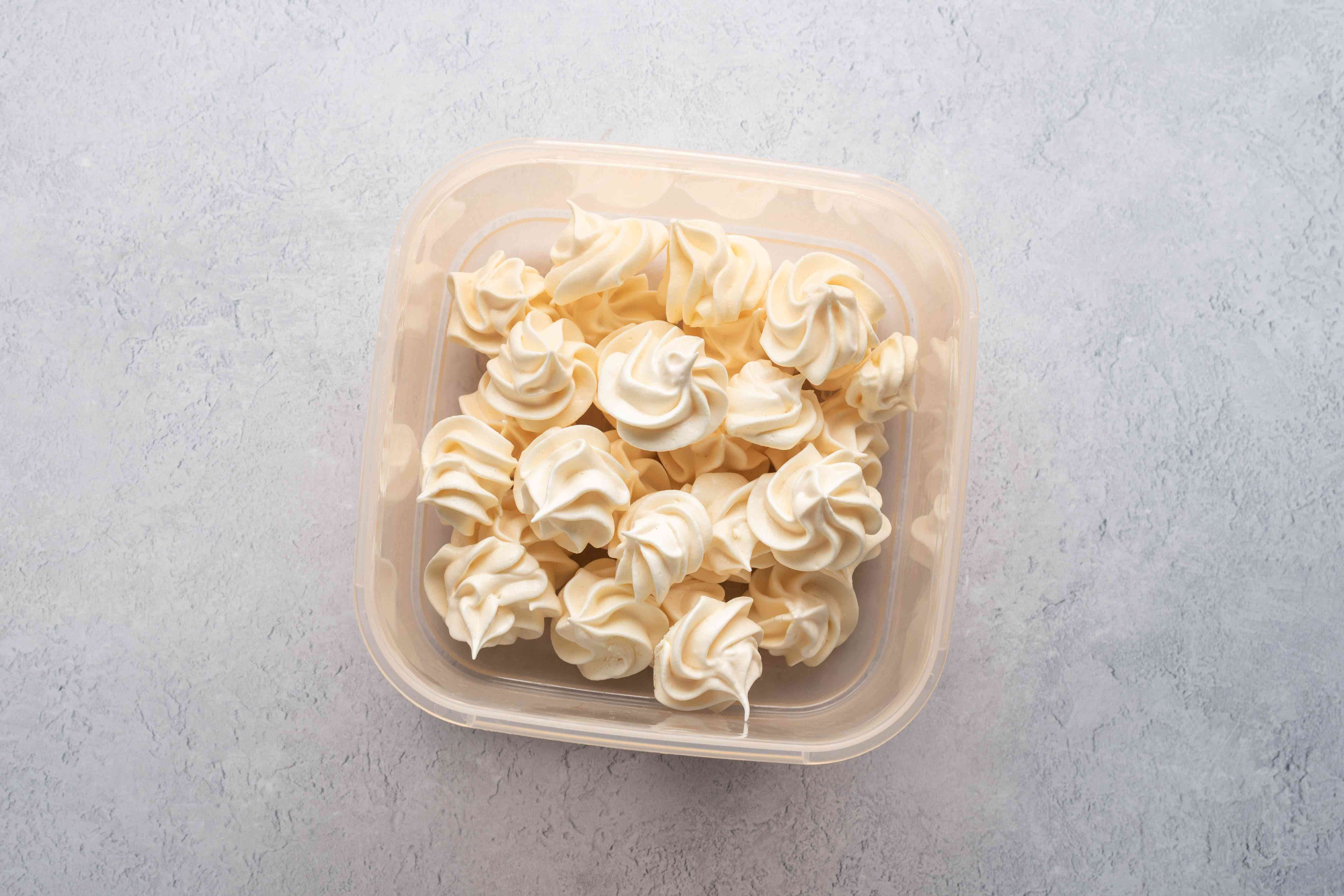 A storage container filled with meringue kisses