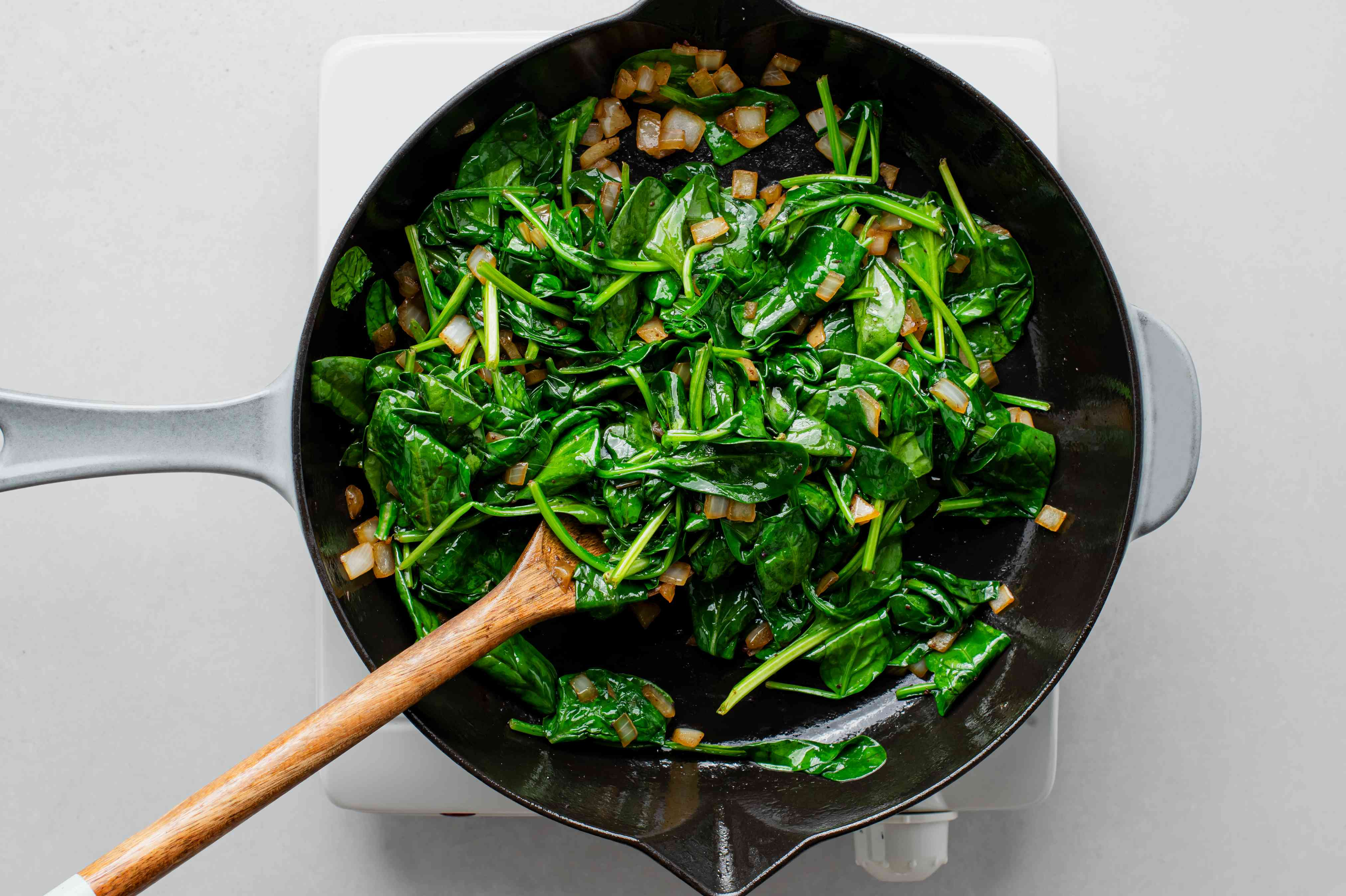 onions and spinach cooking in a skillet