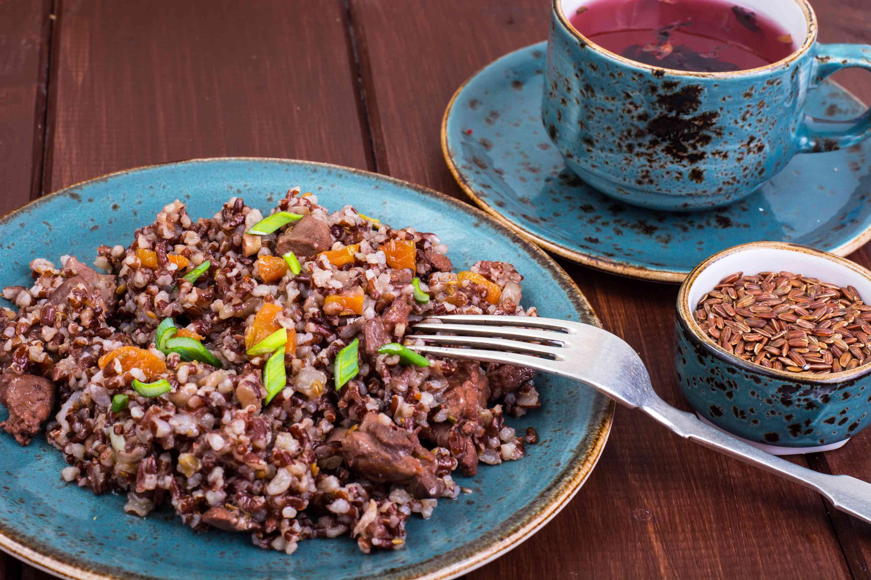 Garnish of red rice, garlic, vegetables, chicken meat