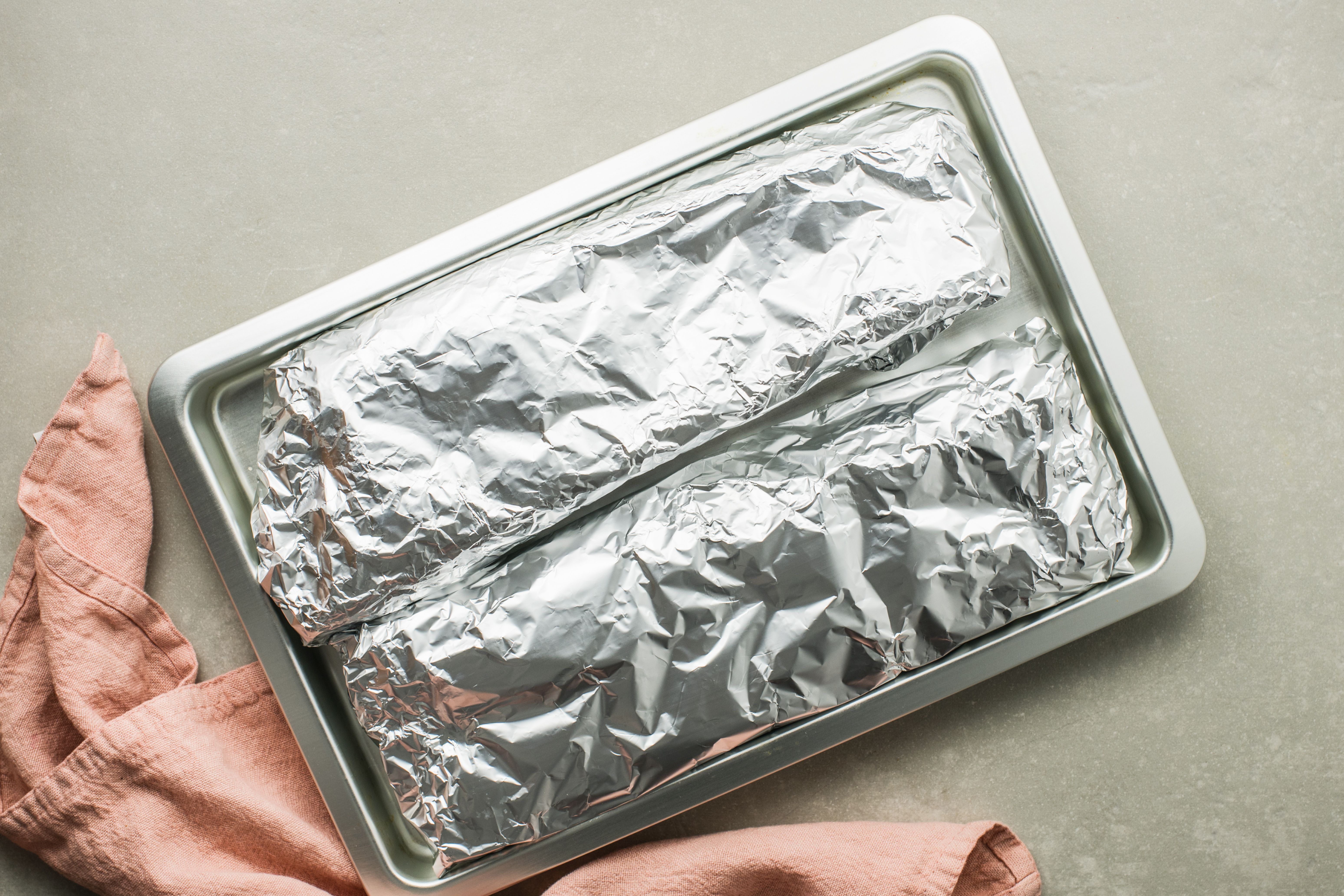 Ribs wrapped in foil on a baking sheet