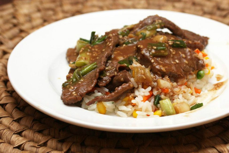 Crock pot teriyaki steak over a bed of rice and vegetables