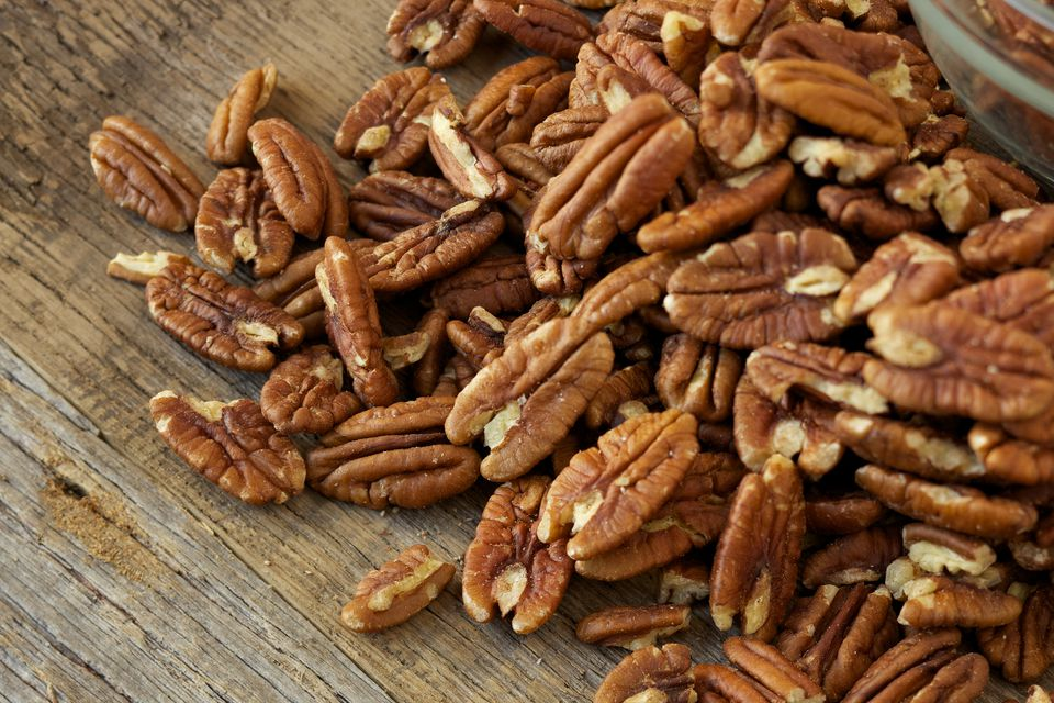 Pecan nuts on rustic wood table