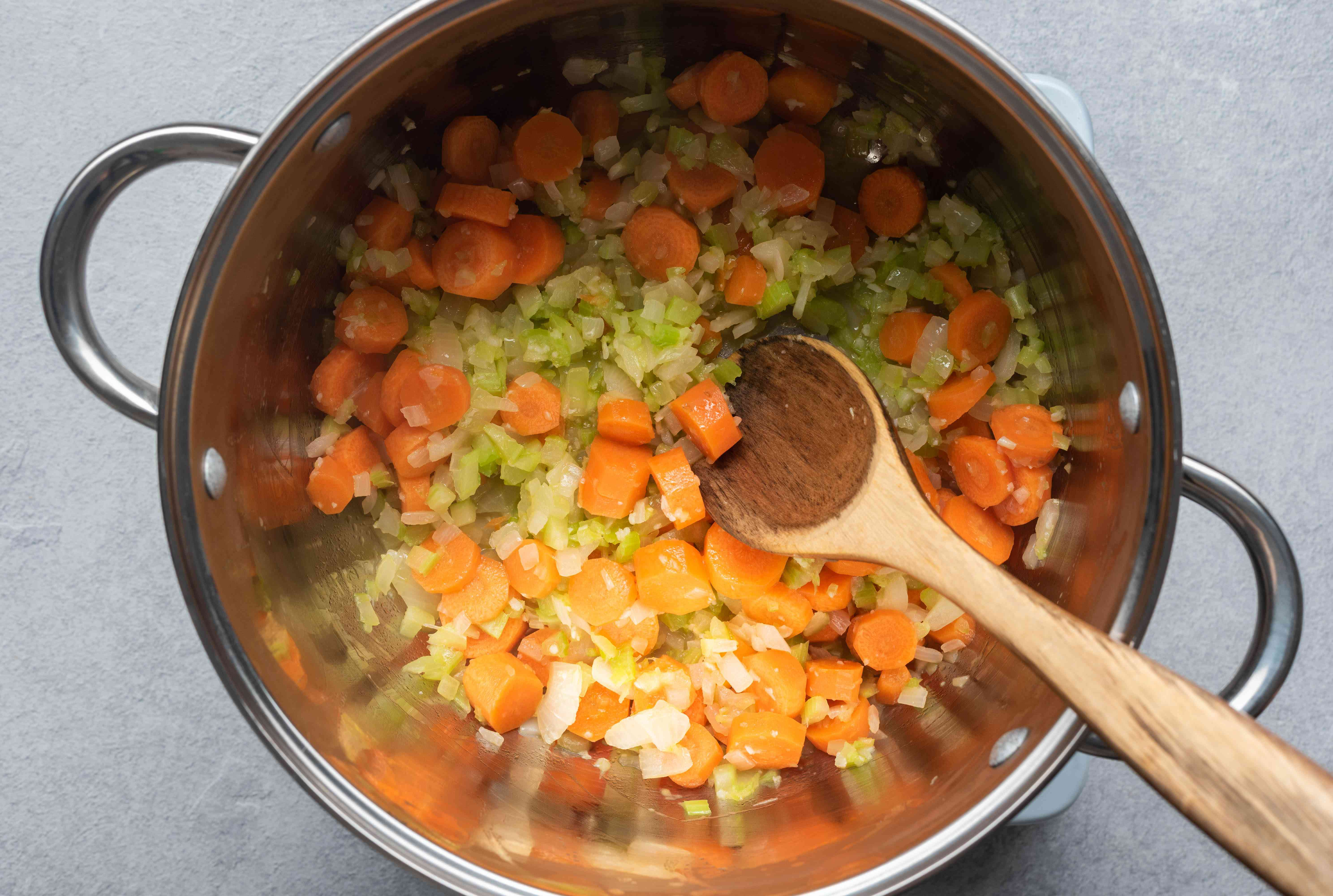 Cook carrots and celery with the onion in the pot