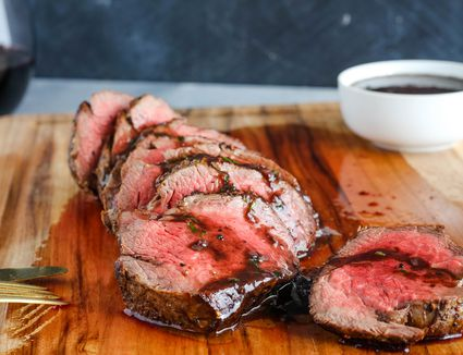 Slicing classic French chateaubriand on a wooden cutting board