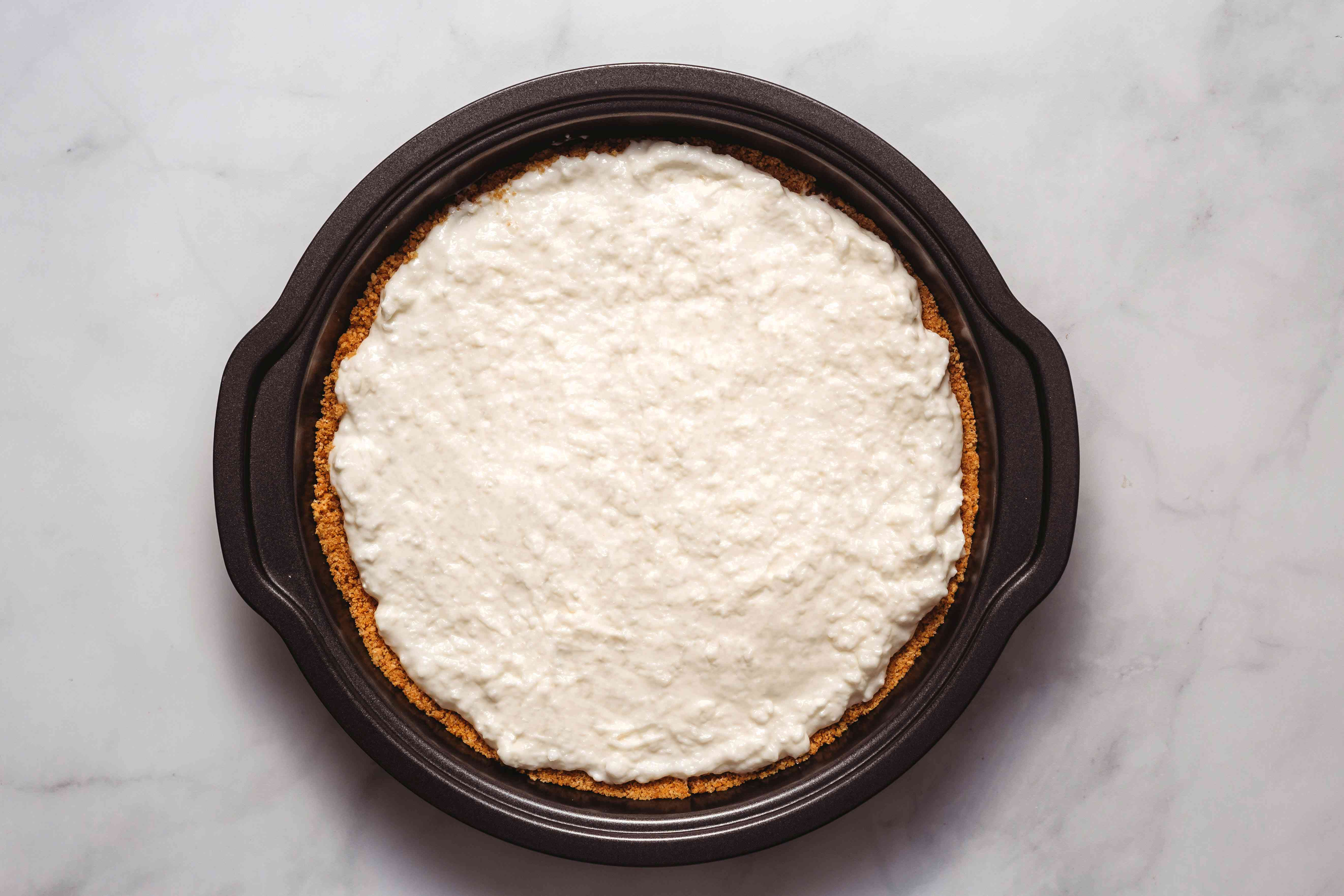 cream cheese filling on top of the crust in a cake pan