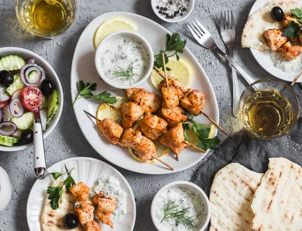 Yogurt marinated grilled chicken skewers with vegetables and tzatziki