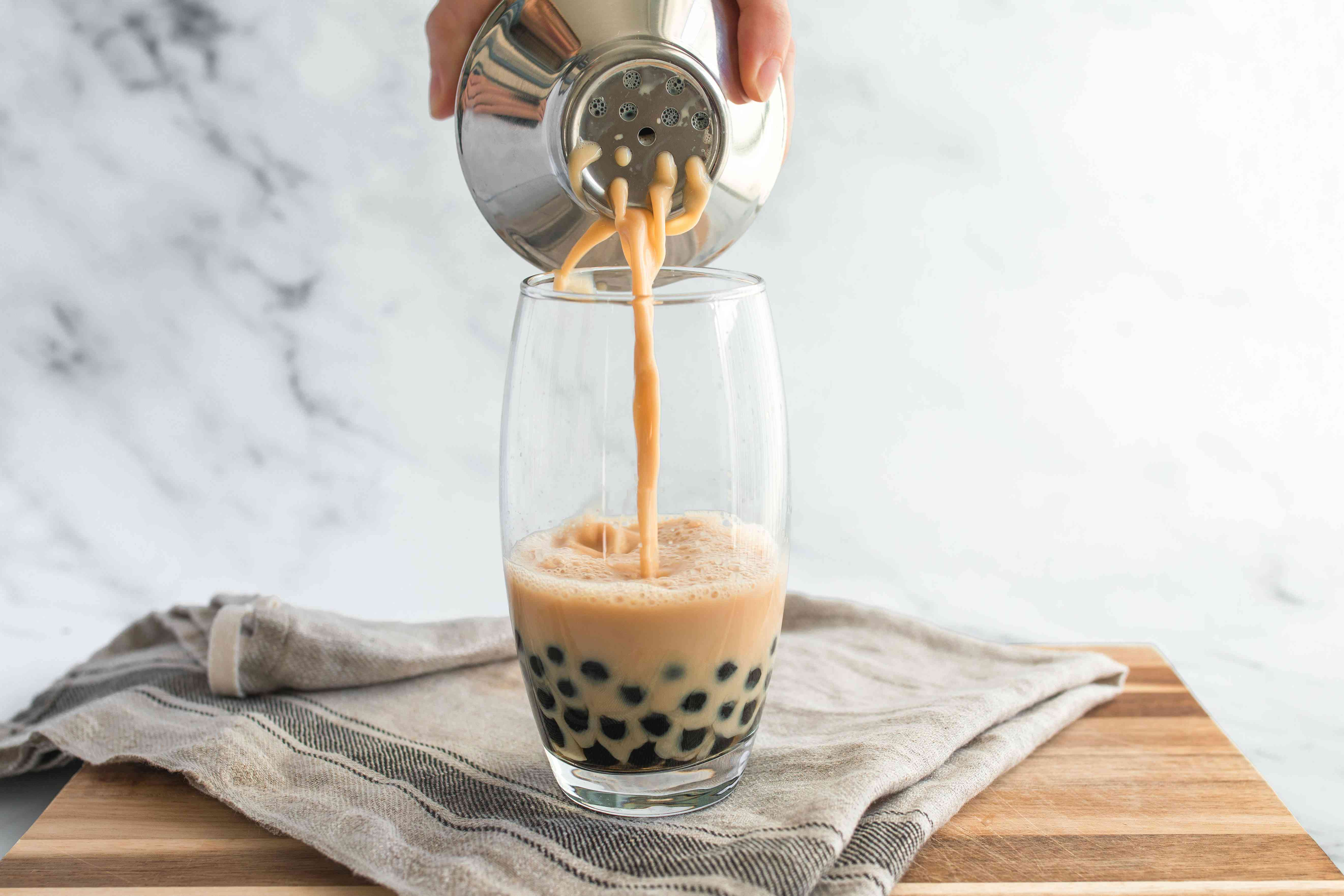 Person pouring liquid into a glass with tapioca pearls.
