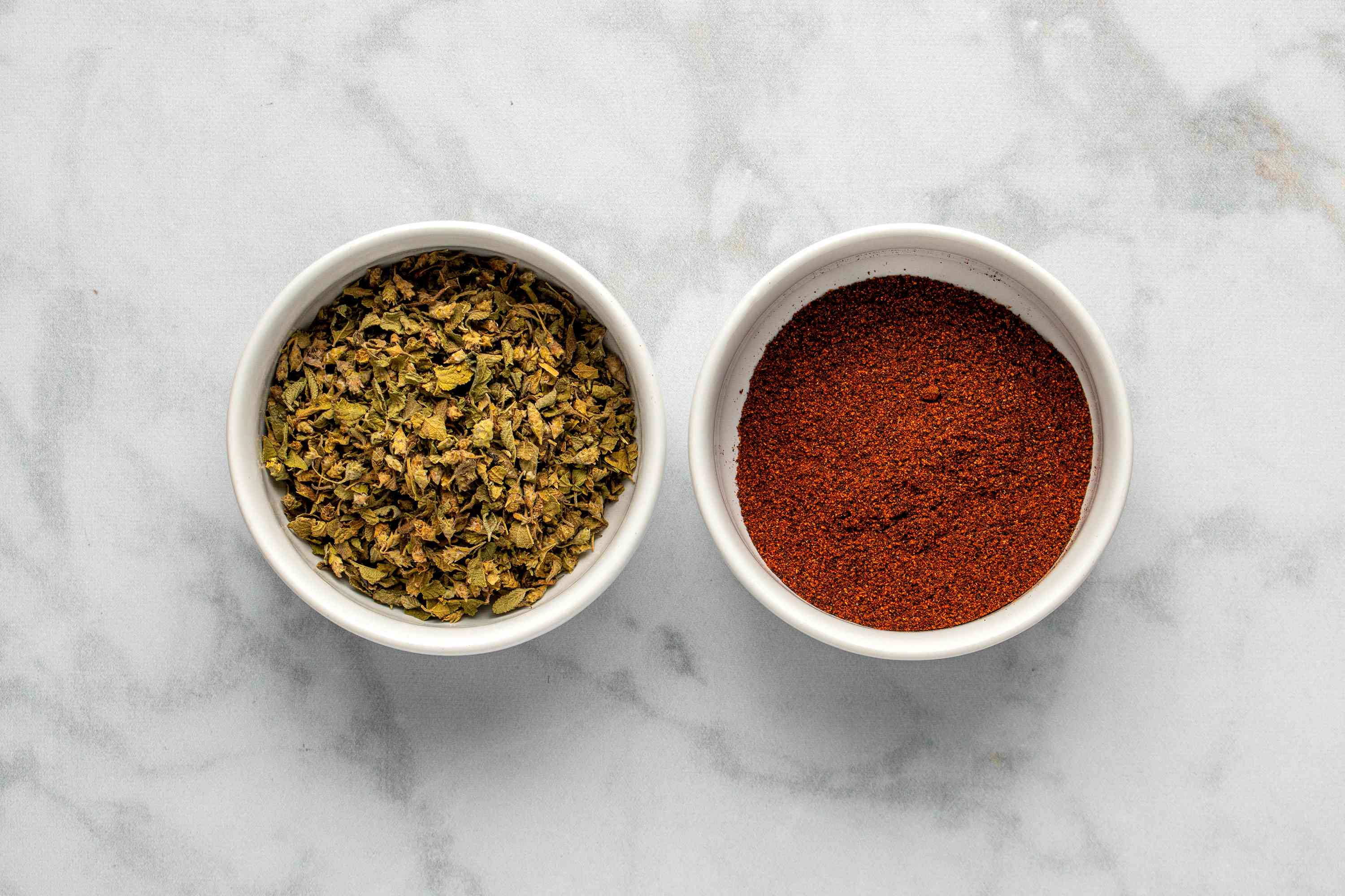 dried oregano and ground chile pepper in bowls