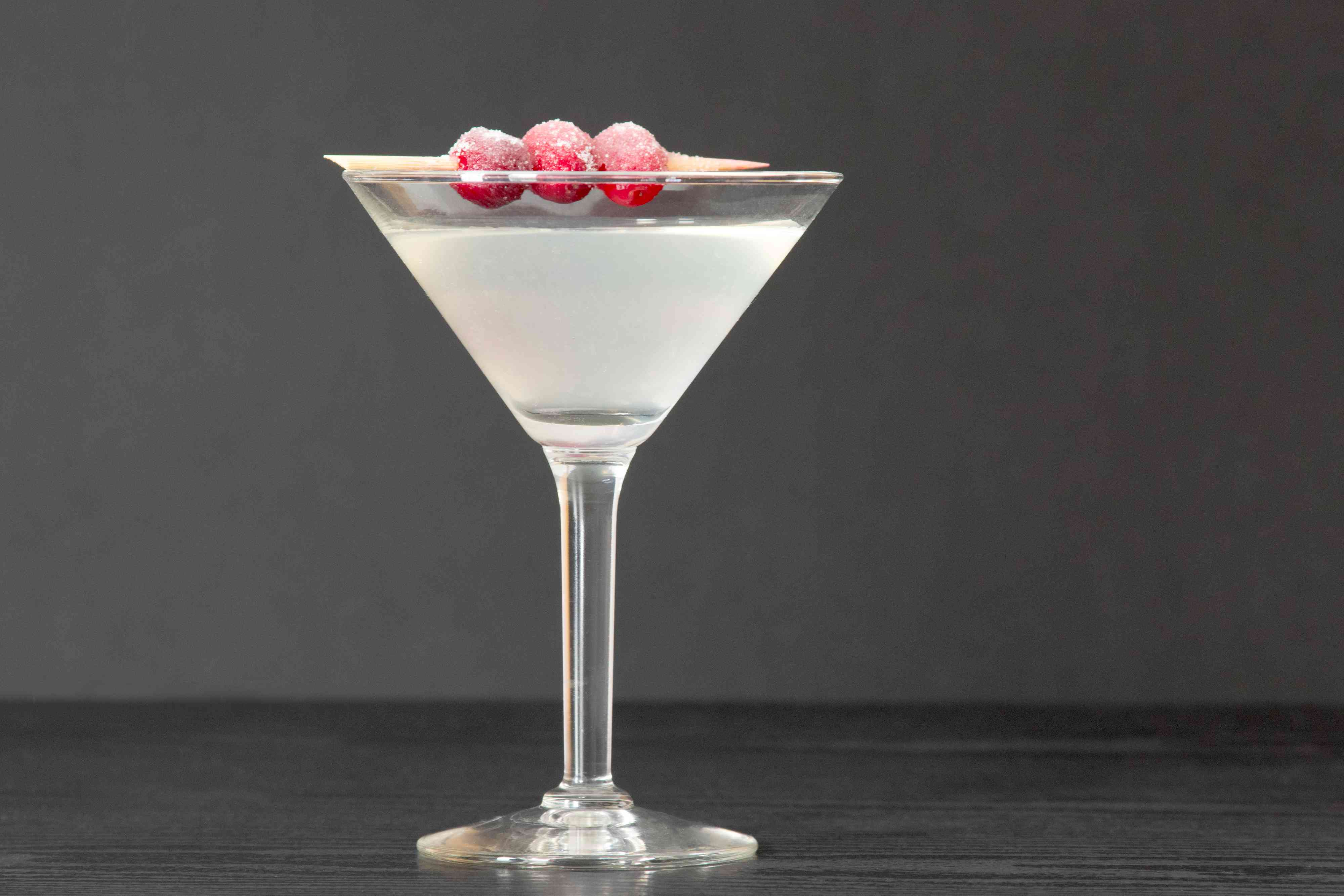 White Cosmo Cocktail With Sugar-Dusted Cranberry Garnish