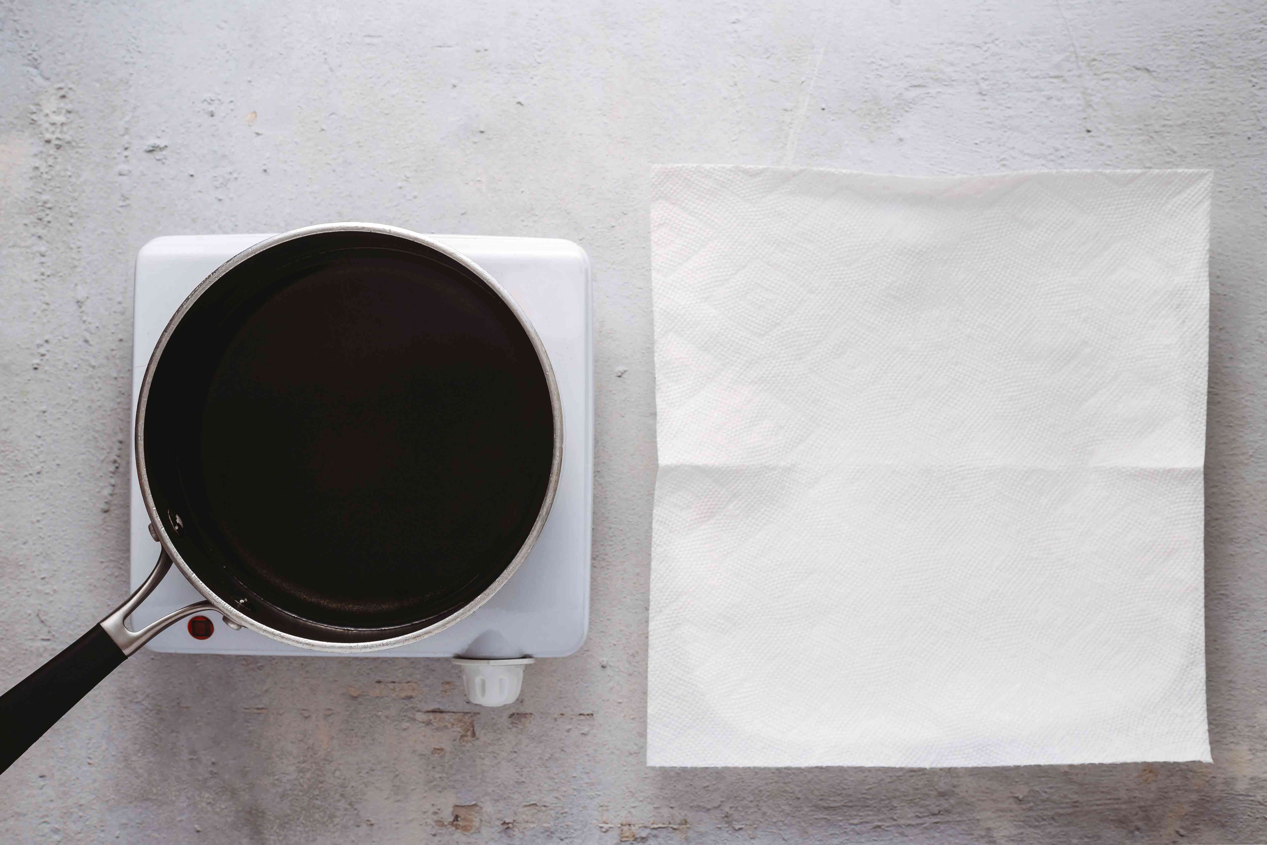 pan with oil on the burner, paper towel