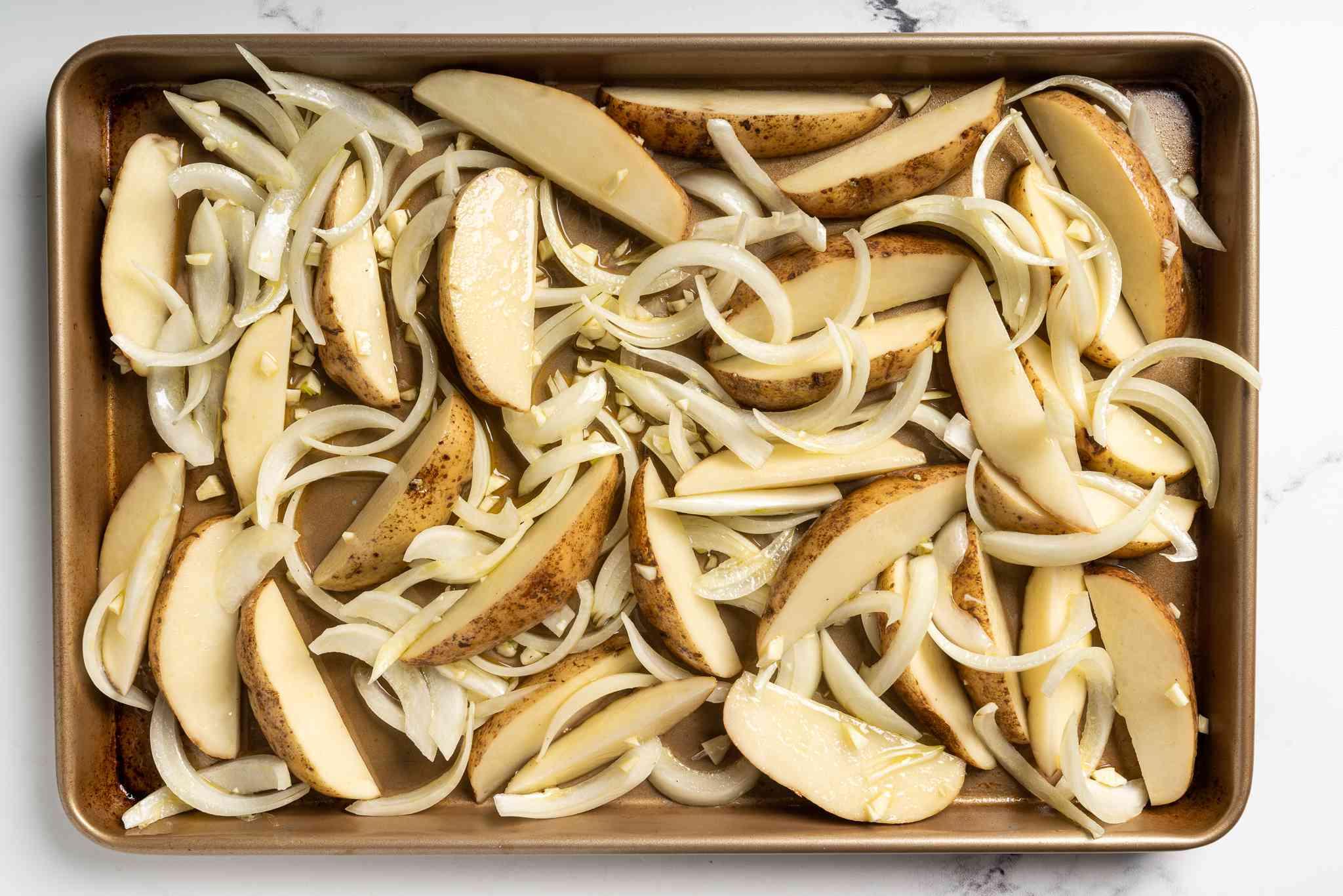 potatoes, onions and garlic on the baking sheet