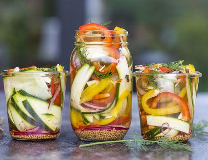 Pickeled vegetables and herbs in preserving jar