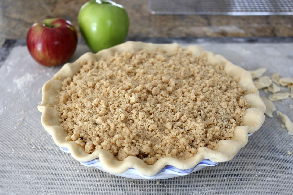 Apple Crisp Pie on a countertop with apples