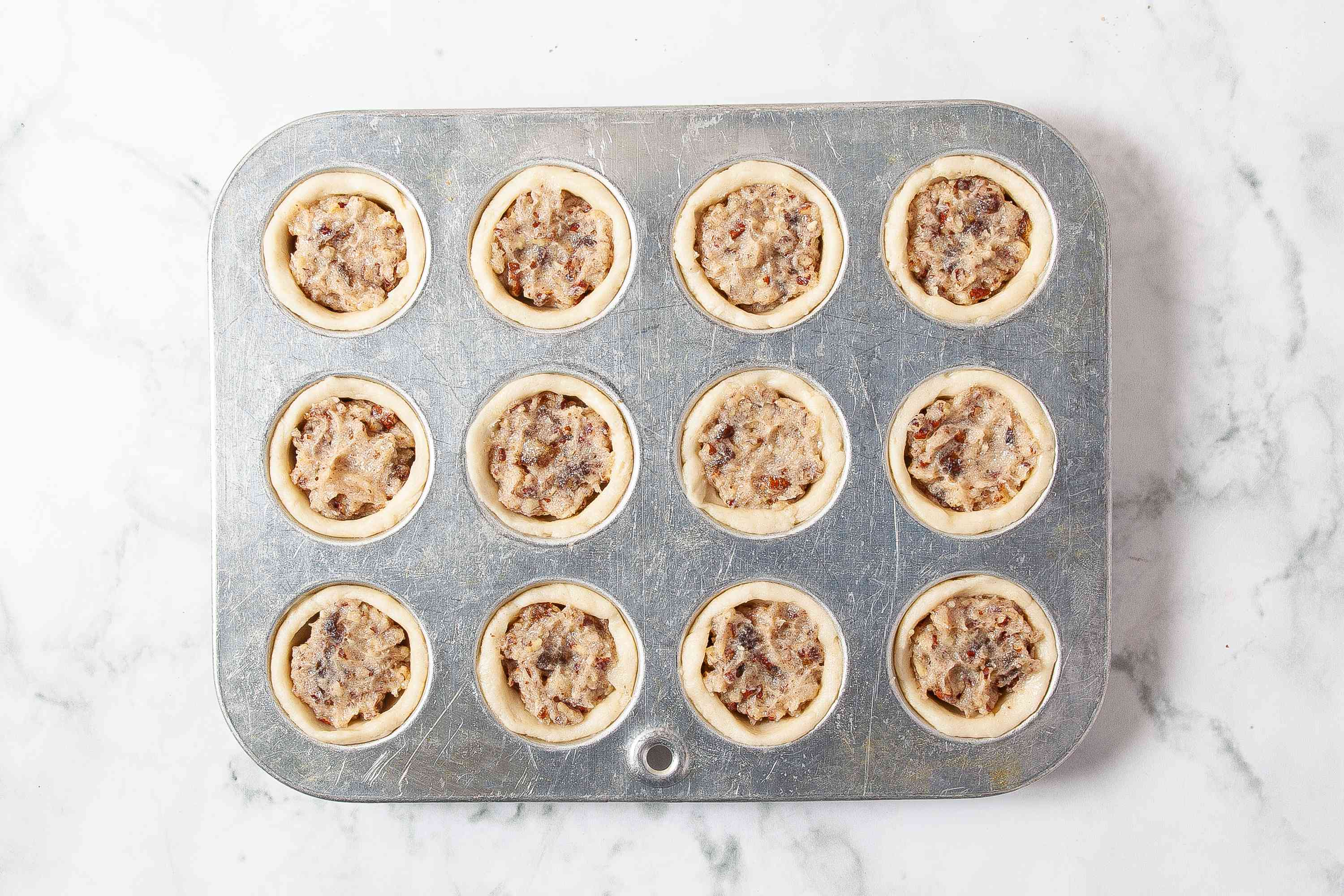 Pecan Tassies unbaked in a muffin tin