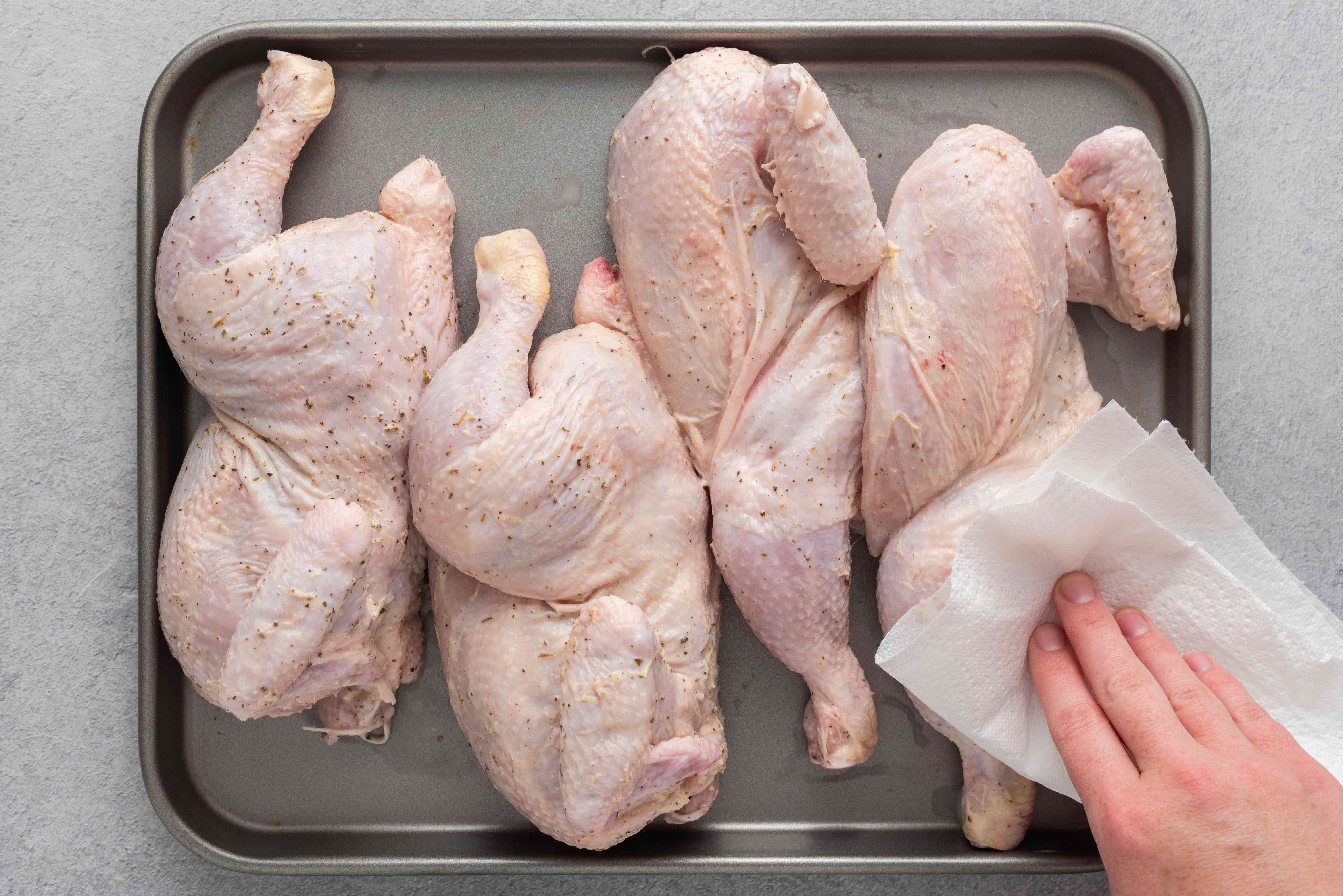 chicken on a baking sheet, pat the chicken with a paper towel to wipe off excess sauce