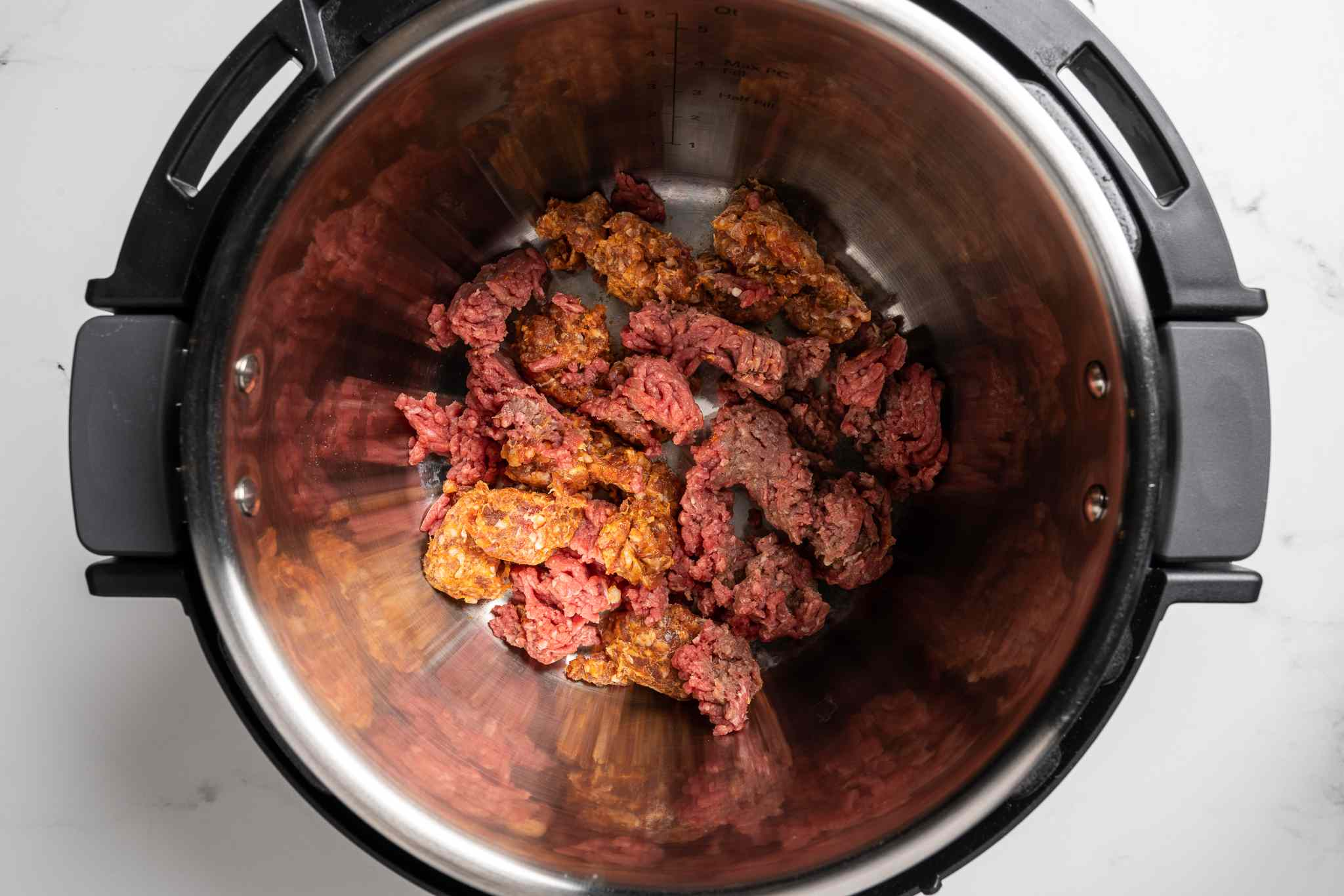 beef and sausage cooking in a pressure cooker