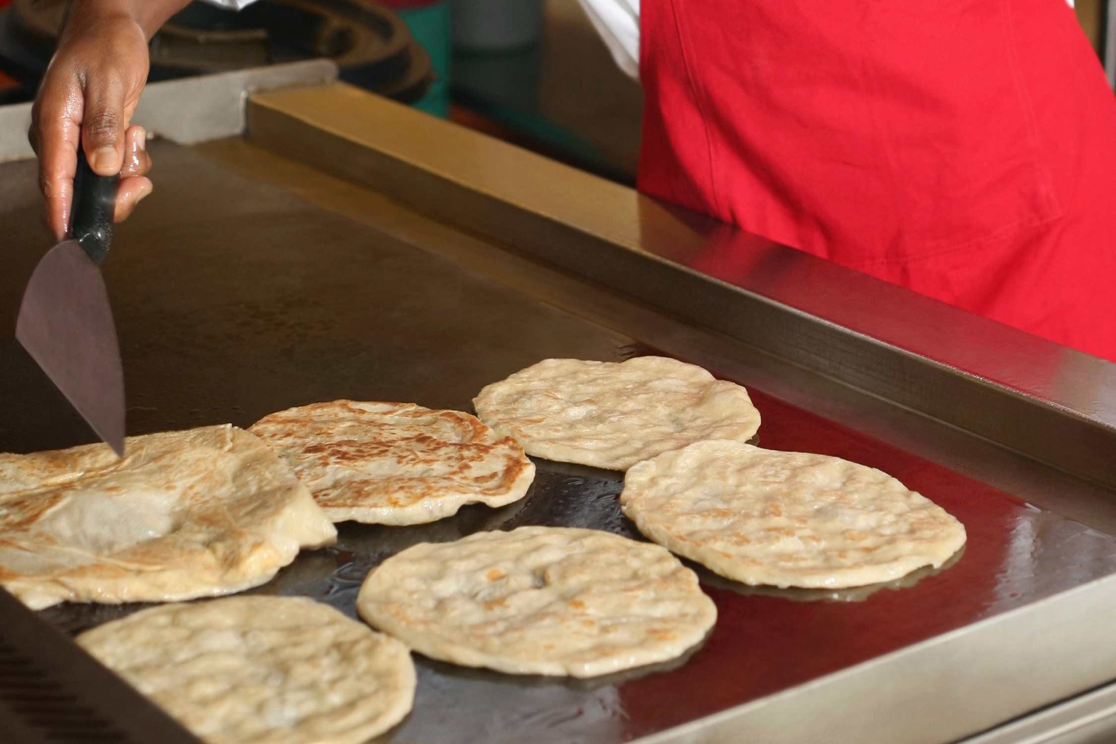 Cooking roti canai on an oiled griddle