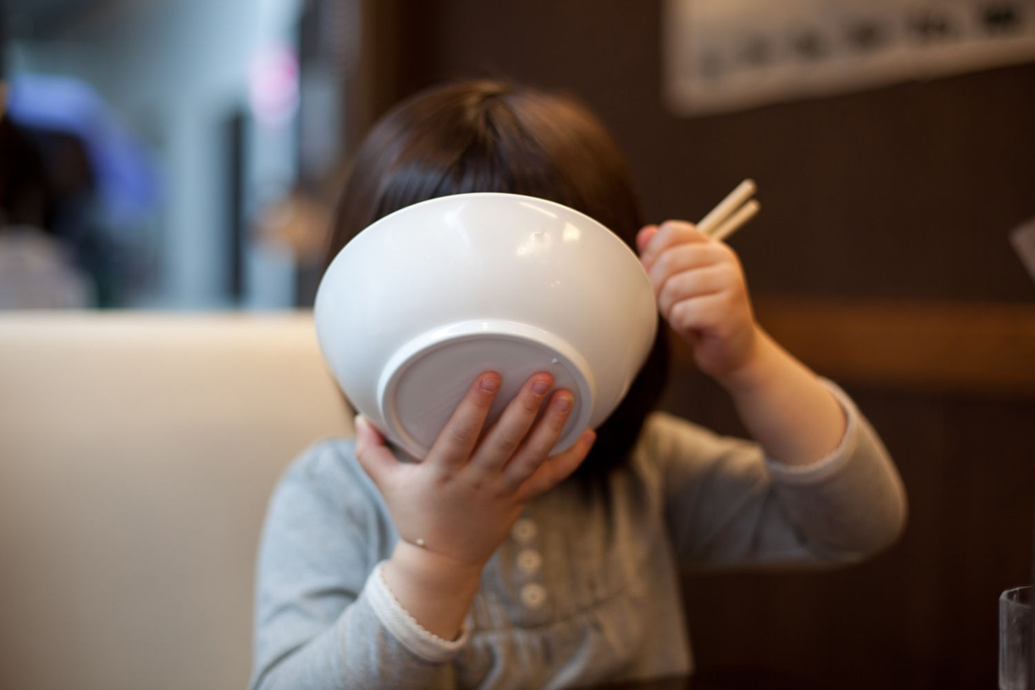 girl eating with bowl to face
