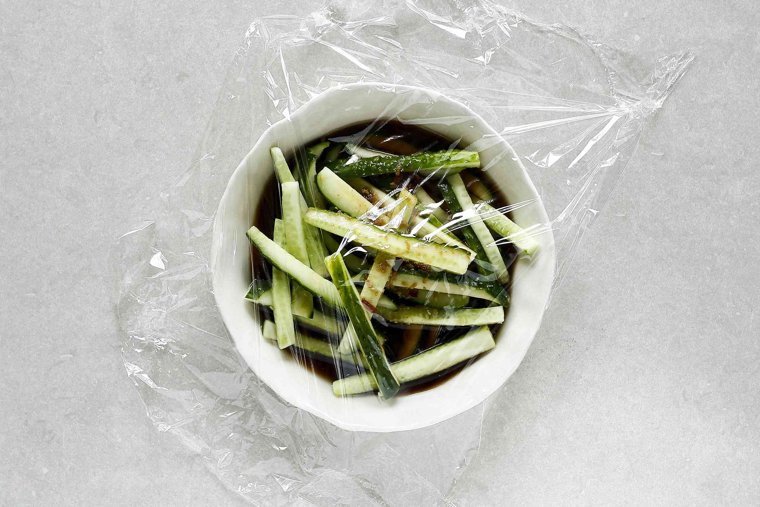Chinese Cucumber Salad in a bowl, covered with plastic