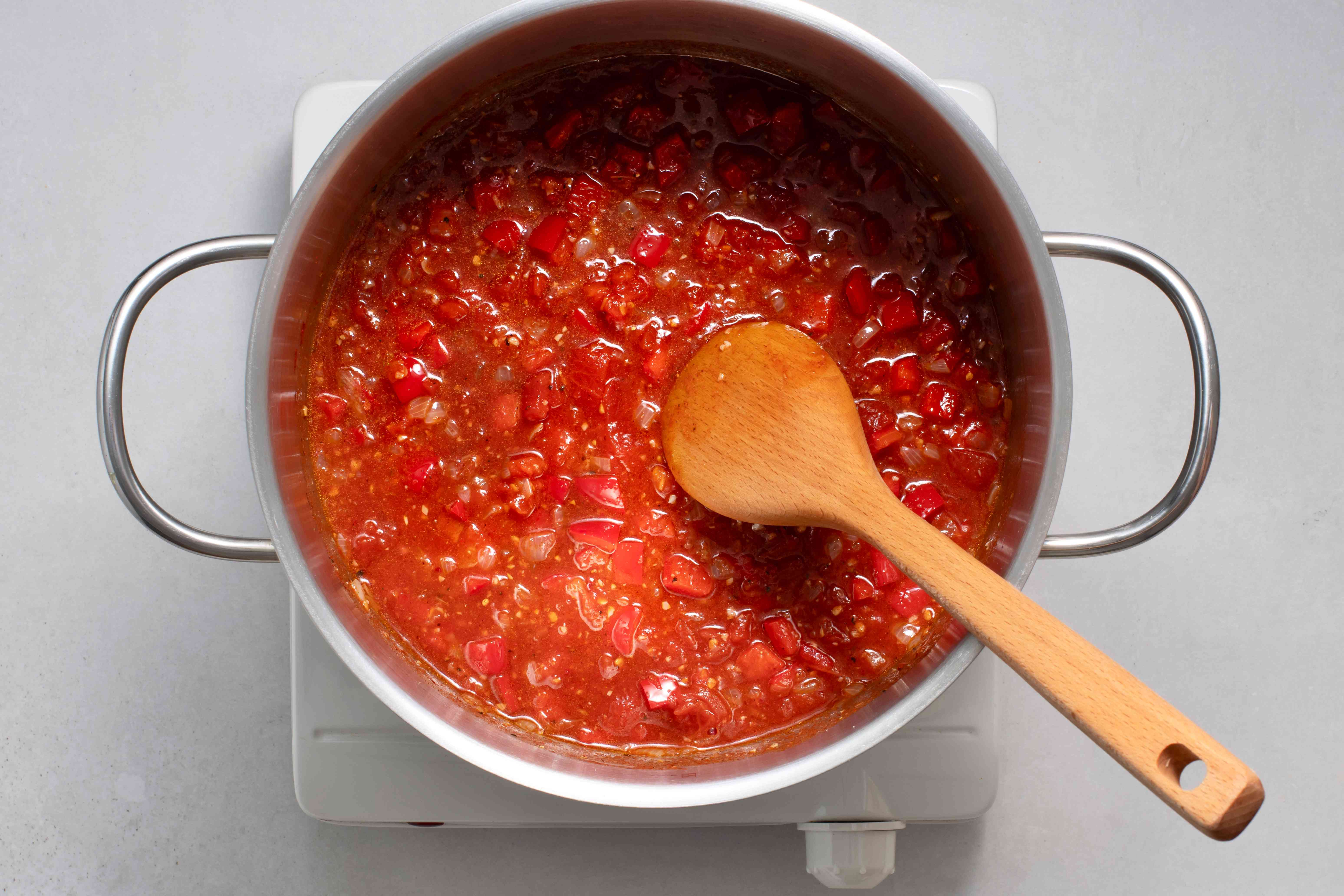 Undrained tomatoes, vegetable broth, and the chili powder in pan