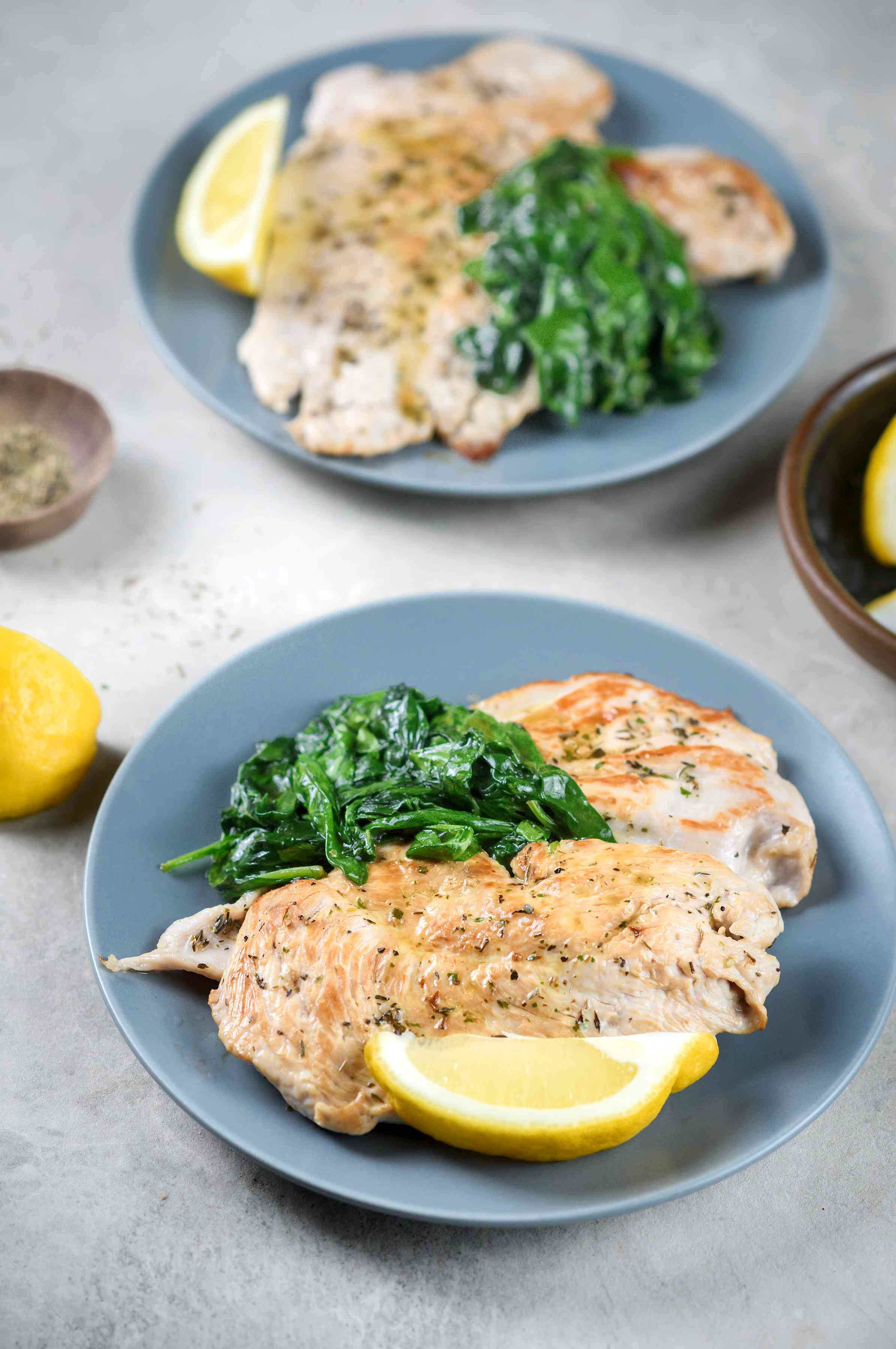 Plated greens, turkey breast, and lemon wedge garnish on plate