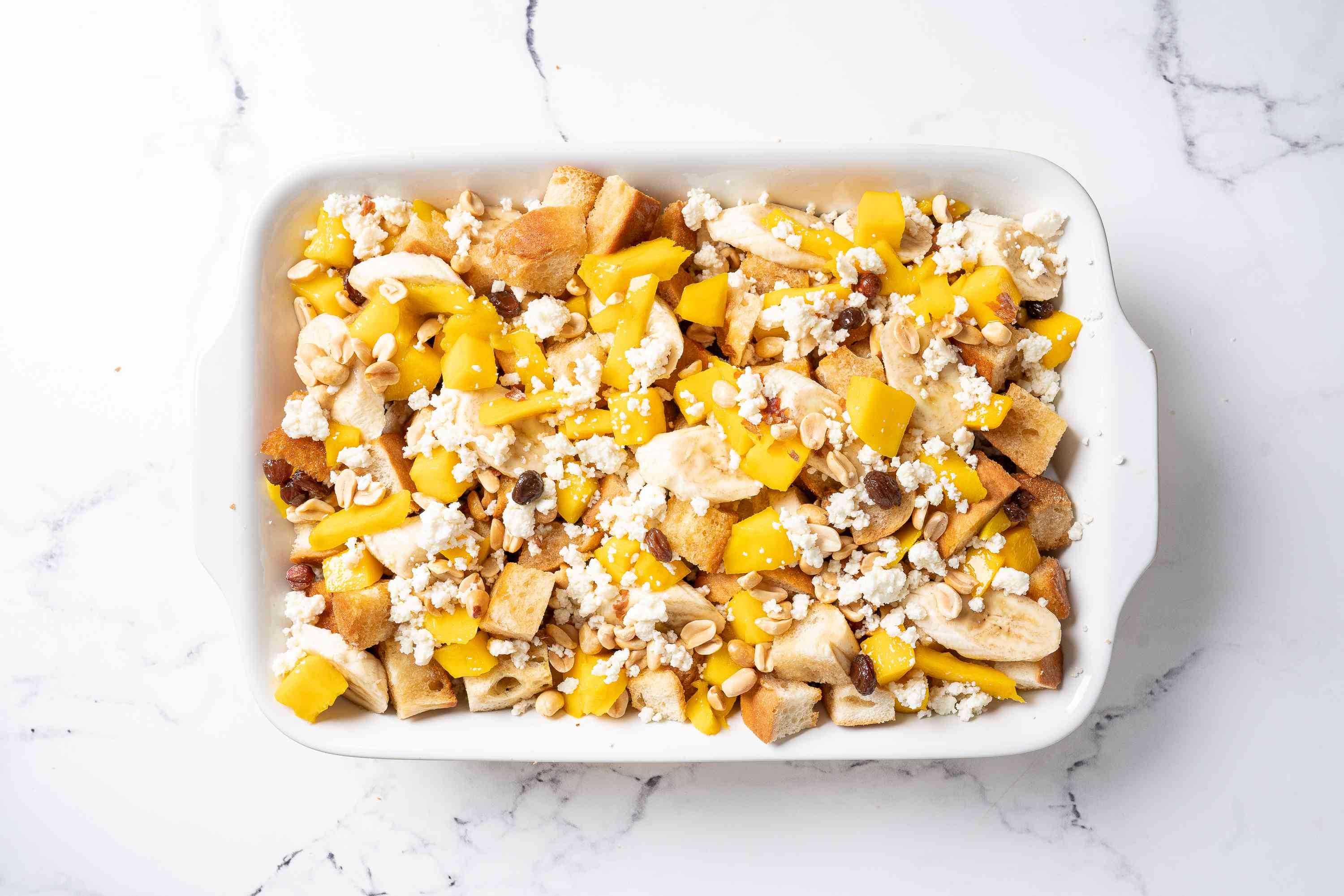 Second layer of bread, fruit, nuts, and cheese in a casserole dish