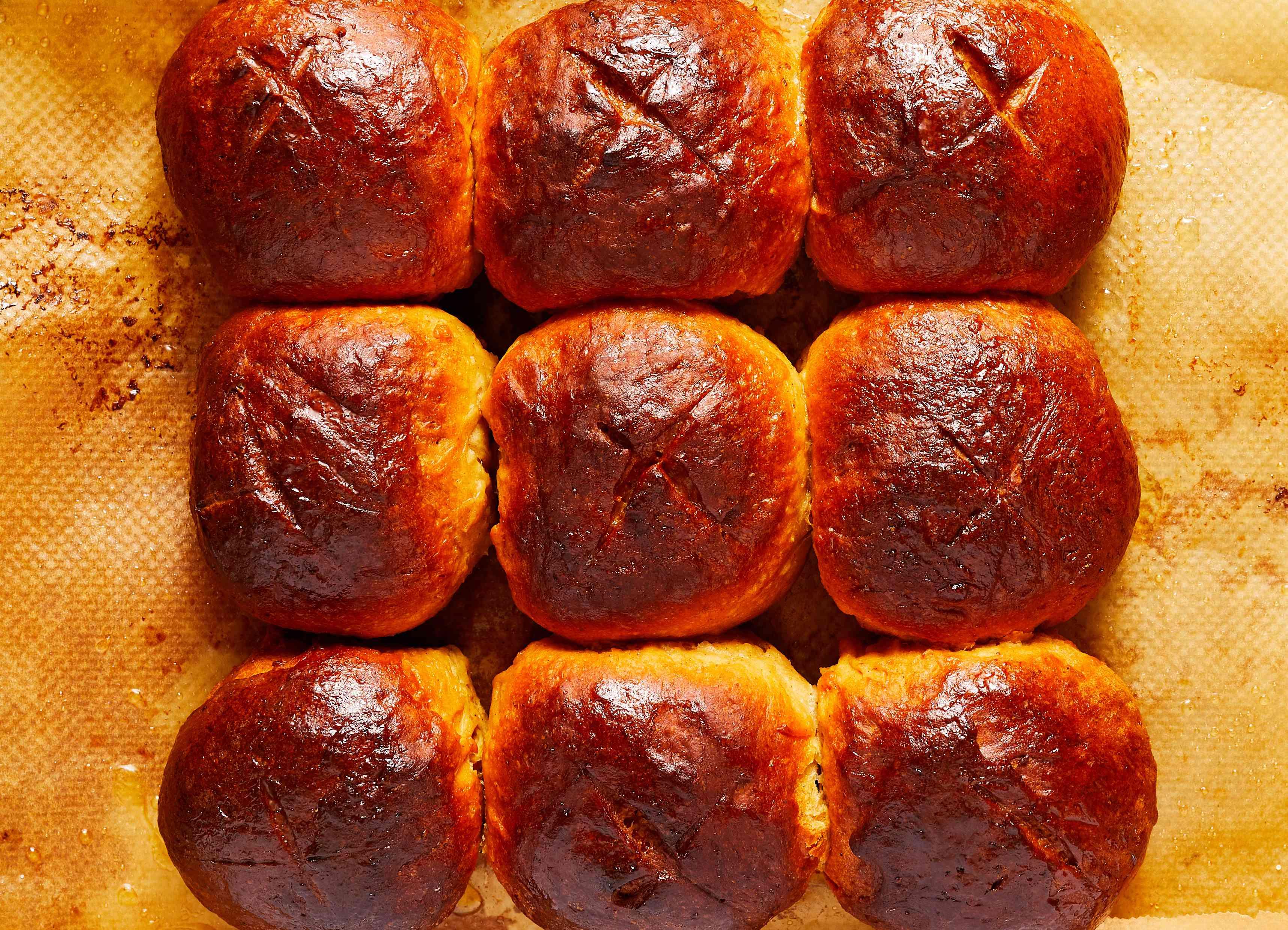 baked hot cross buns on baking sheet, deep golden brown