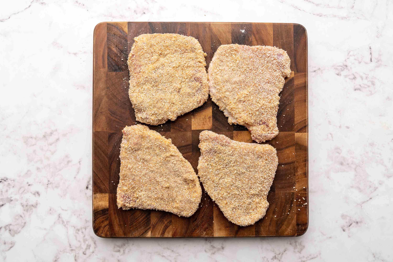 breaded pork cutlets on a cutting board