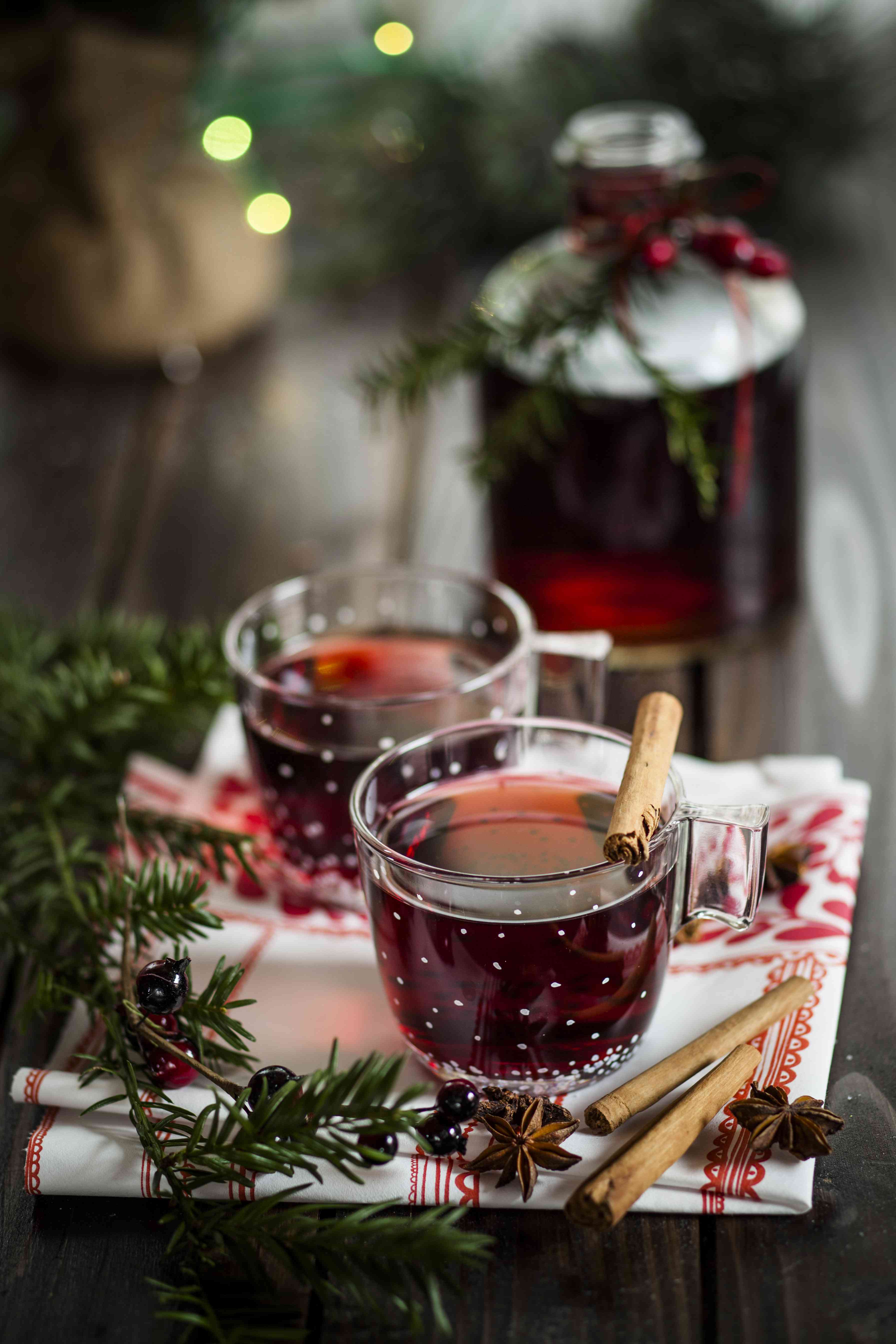 Glasses of mulled wine, spices, and fir branch