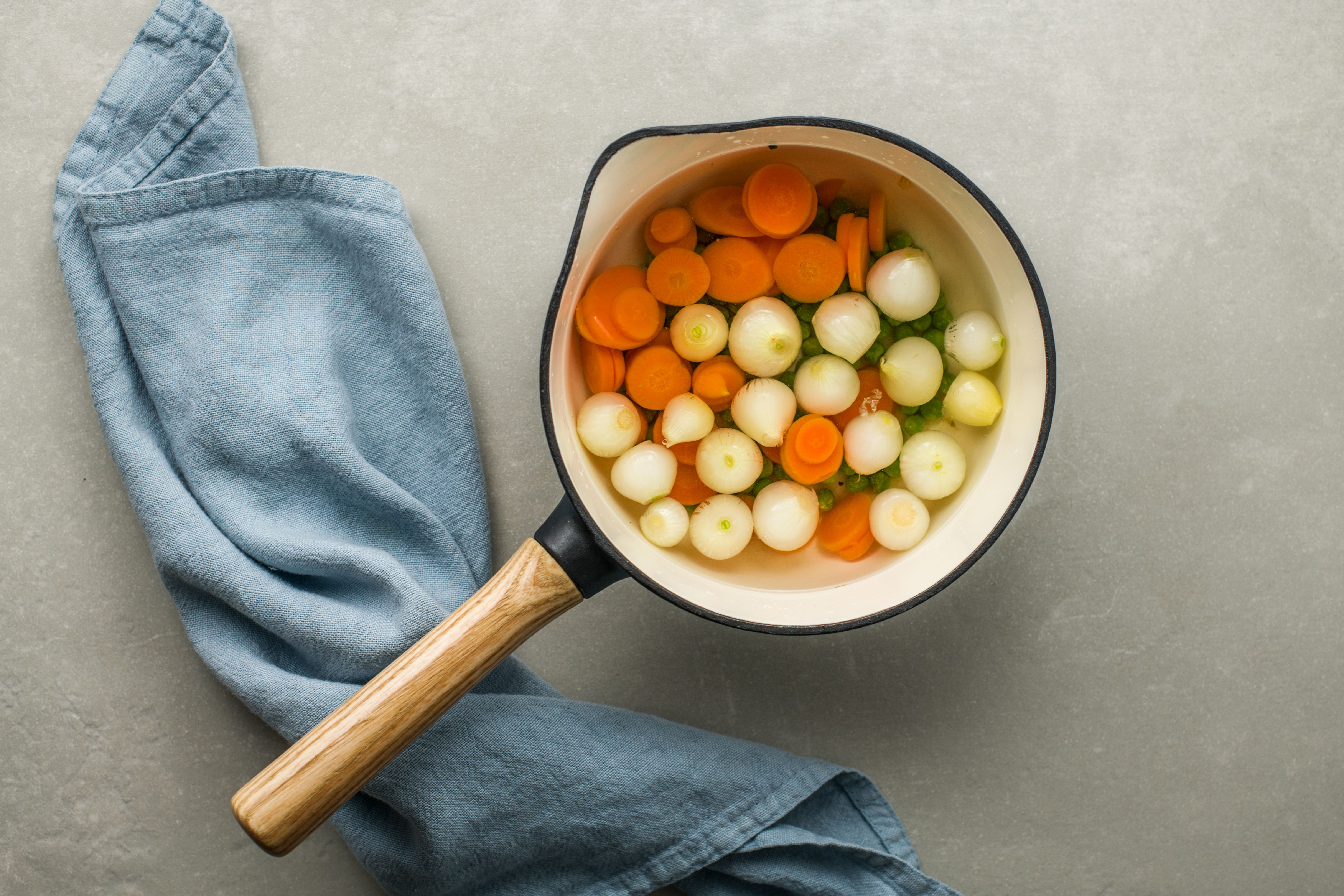 Carrots, peas and onions in a pot with water