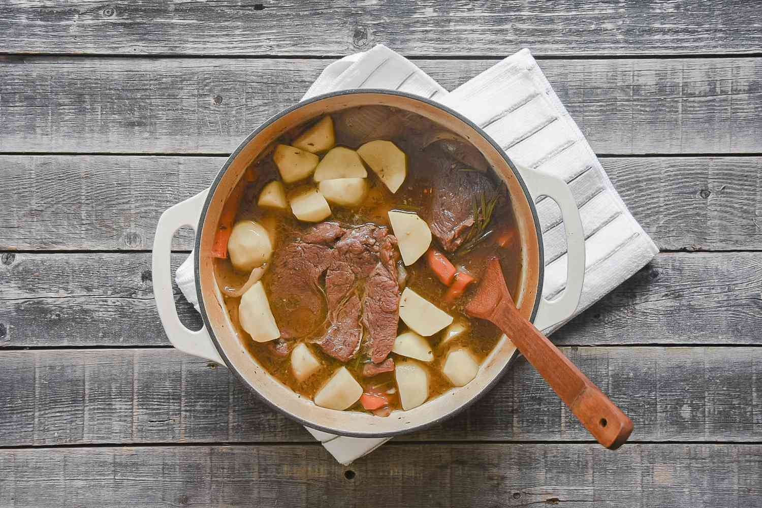 Pot roast with potatoes in a large white pot, with a wooden spoon