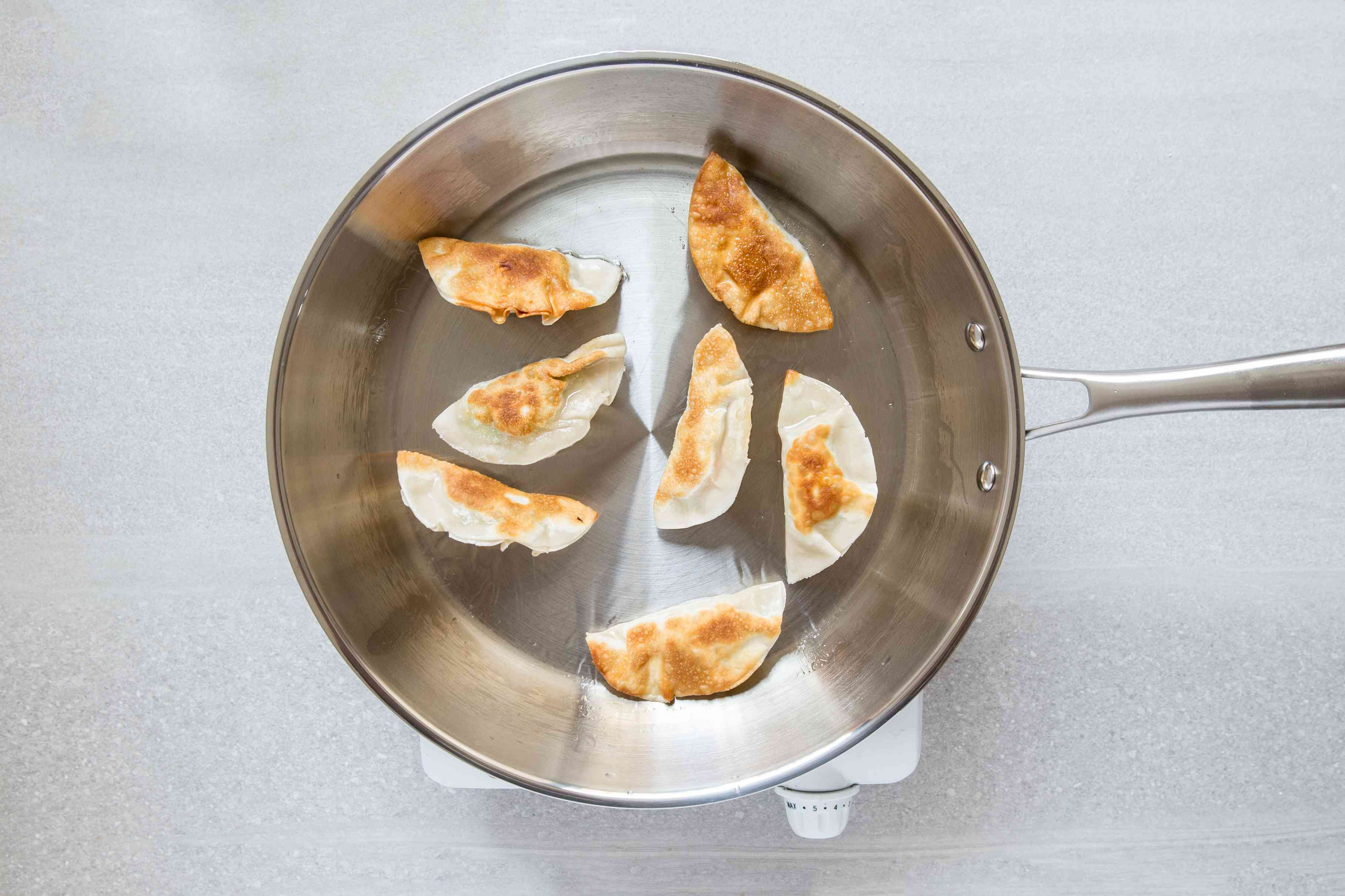 shrimp gyoza cooking in a skillet