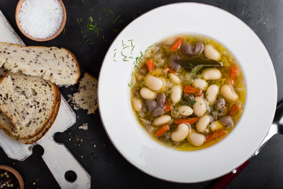 Bean soup in a bowl with herbs and bread