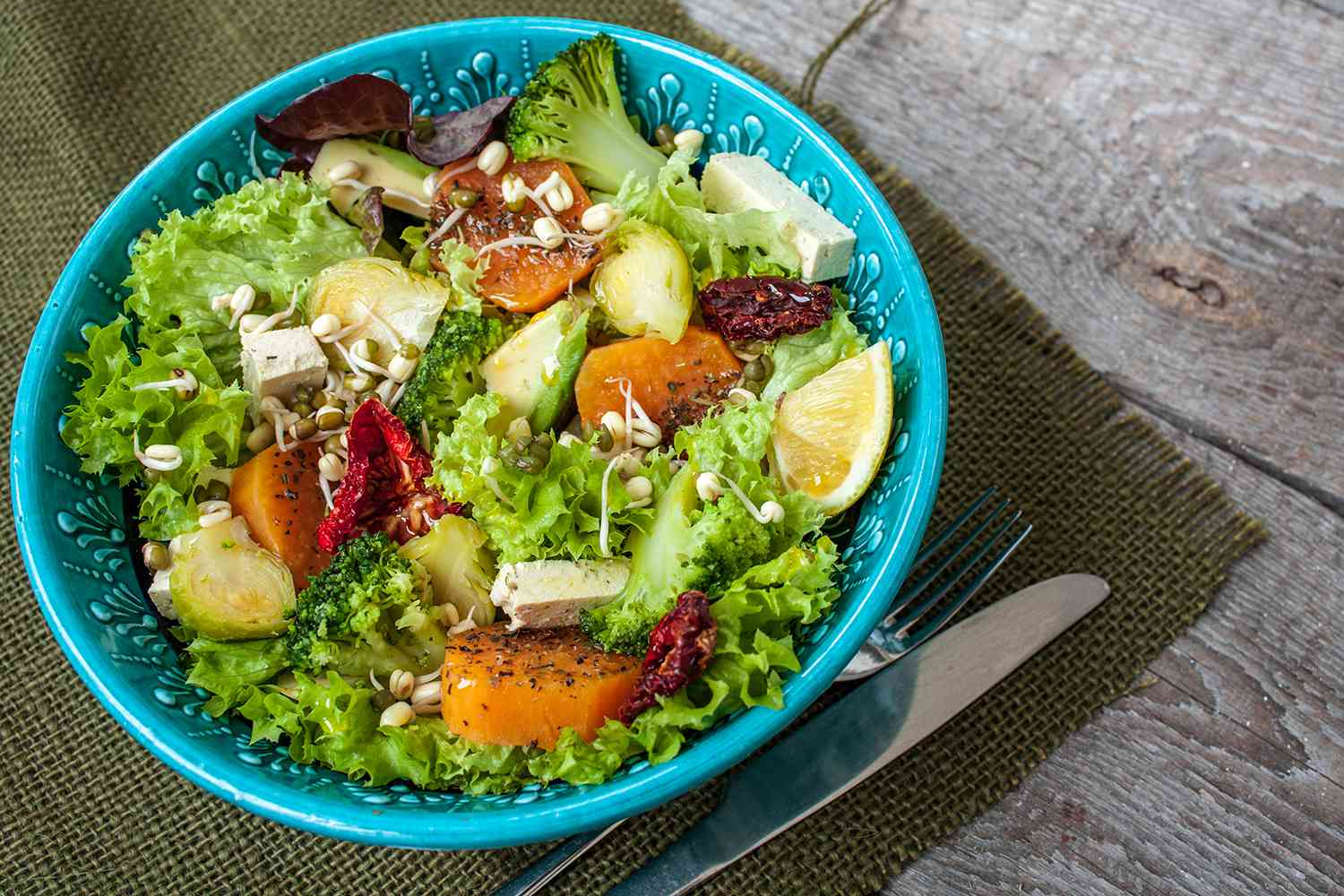 Salad with sweet potatoes, dried tomatoes, avocado, broccoli, brussels sprouts, tofu, mung bean sprouts.