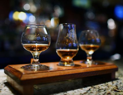 Small glasses of whiskey lined up for a tasting