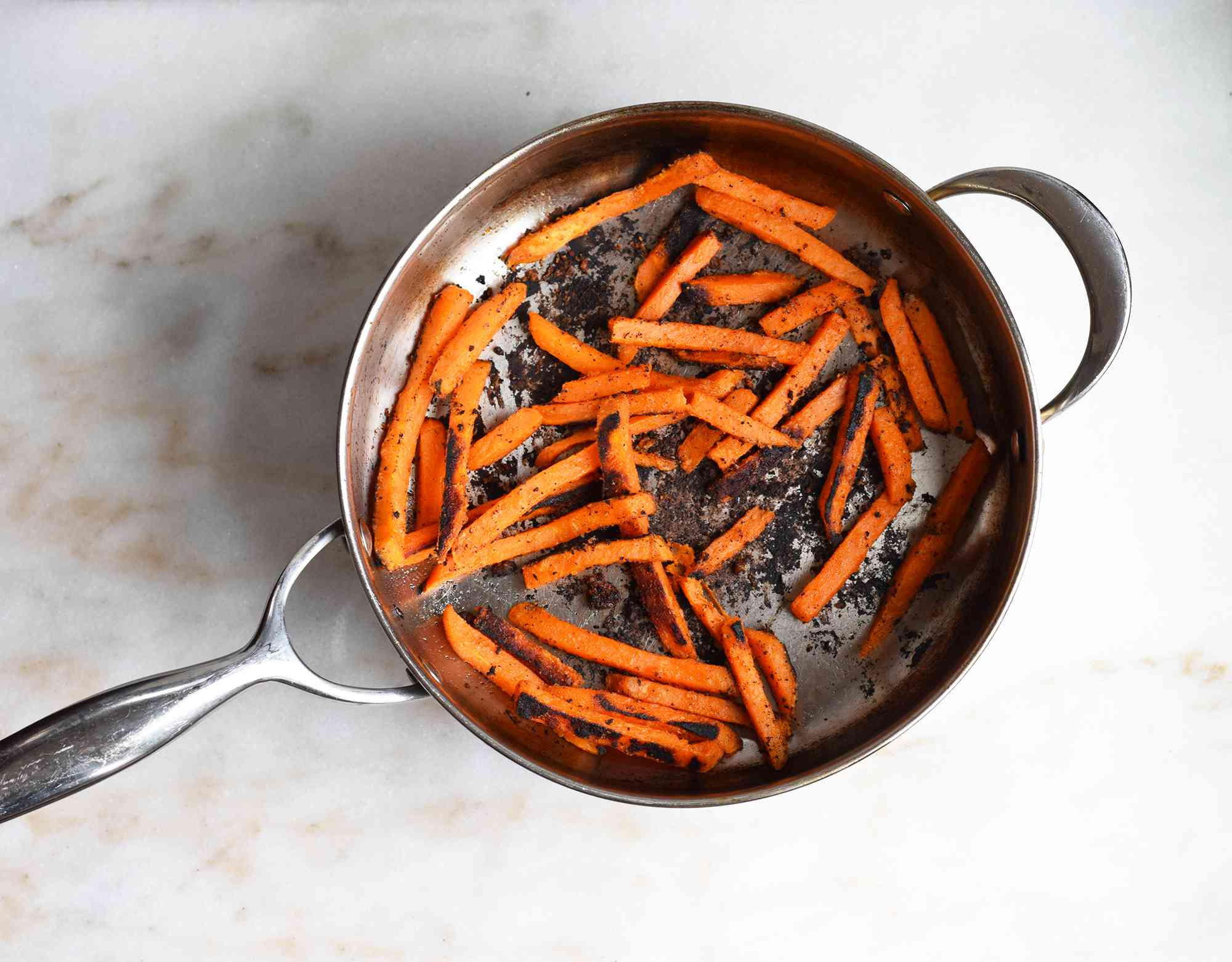 browned sweet potato fries in a saute pan
