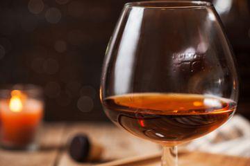 Glass of cognac on dark background - stock photo