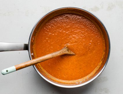 blended tomato sauce in a saucepan with a wooden spoon