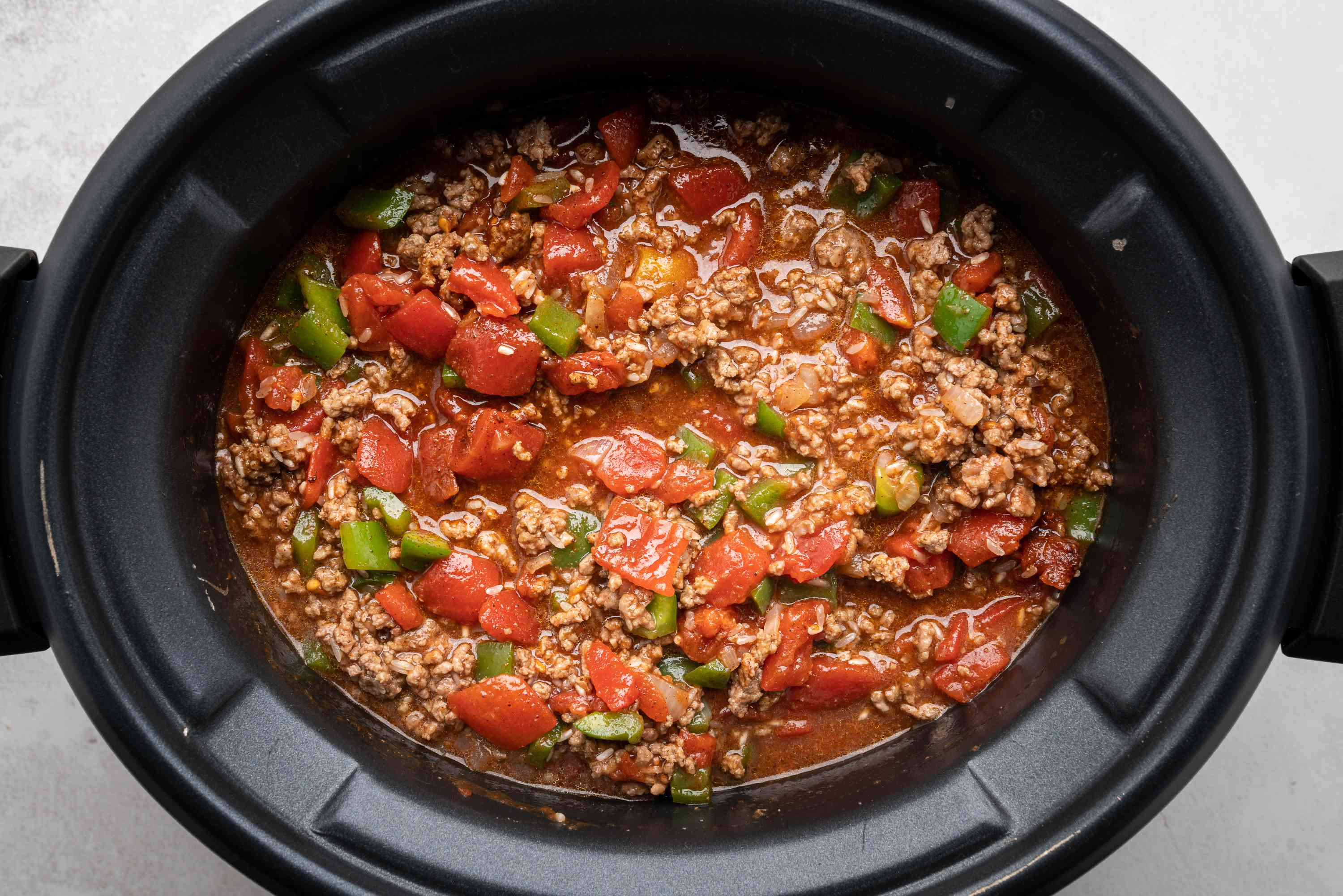 tomatoes, tomato sauce, chili powder, salt, Worcestershire sauce, rice, and water with the beef mixture in a crock pot