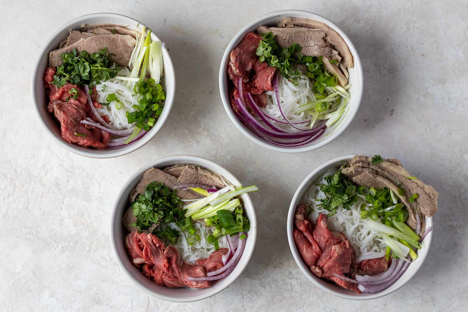 Divide the prepared noodles among the four bowls, top with cooked brisket, raw filet mignon, red onion, green onion, and cilantro
