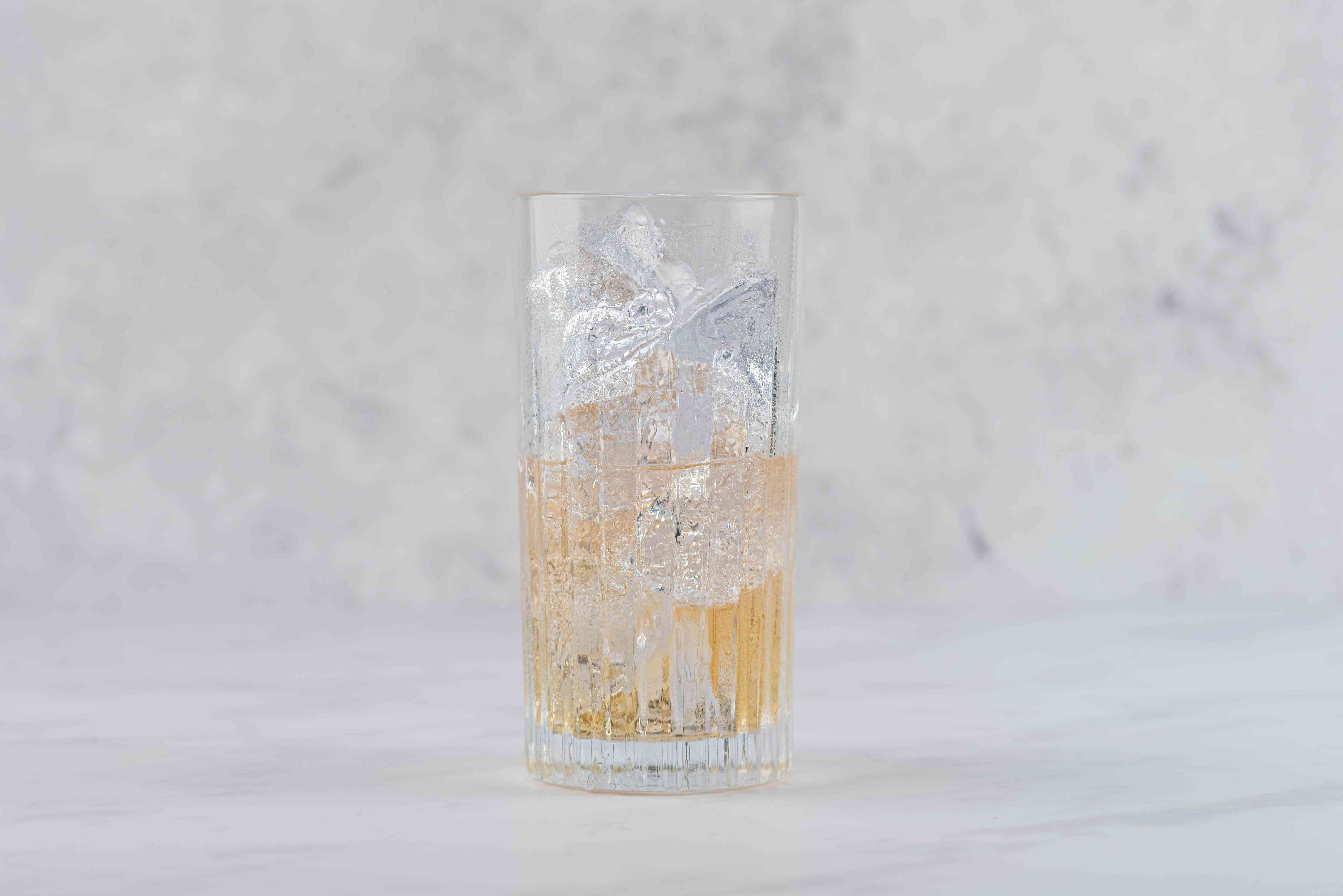 Pour the liqueur and Champagne over ice in a chilled collins glass