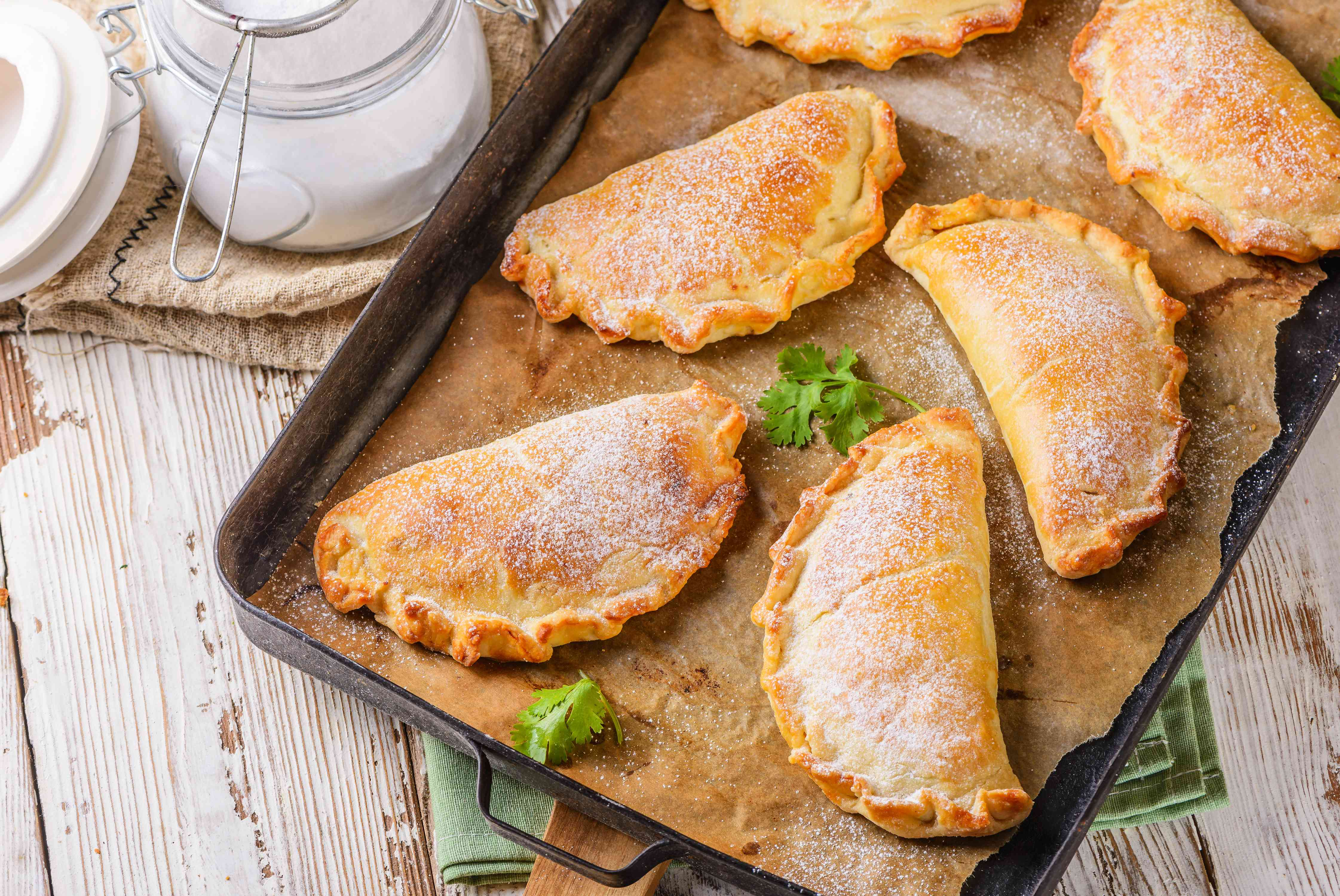 Baked empanadas dusted with powdered sugar