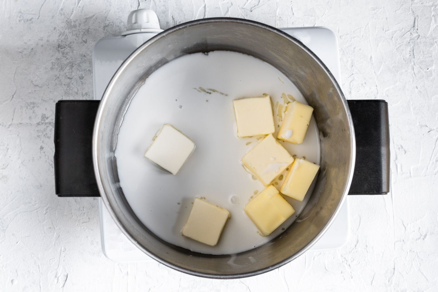 Milk and butter added to the pan used to boil the potatoes