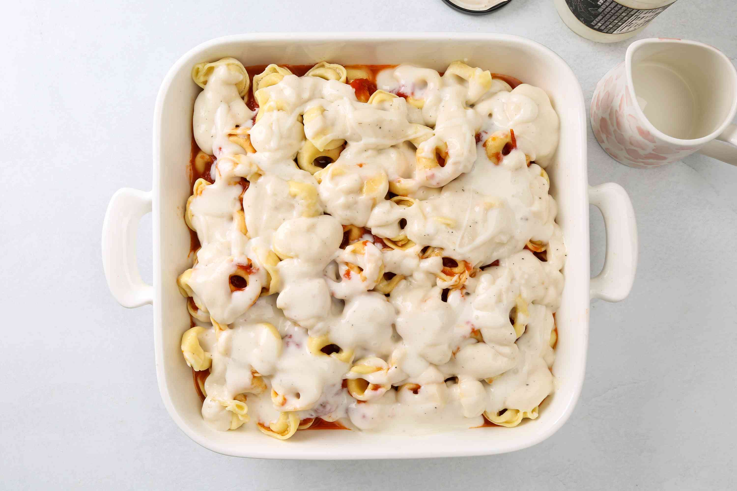 Alfredo sauce on top of the tortellini mixture in the baking dish